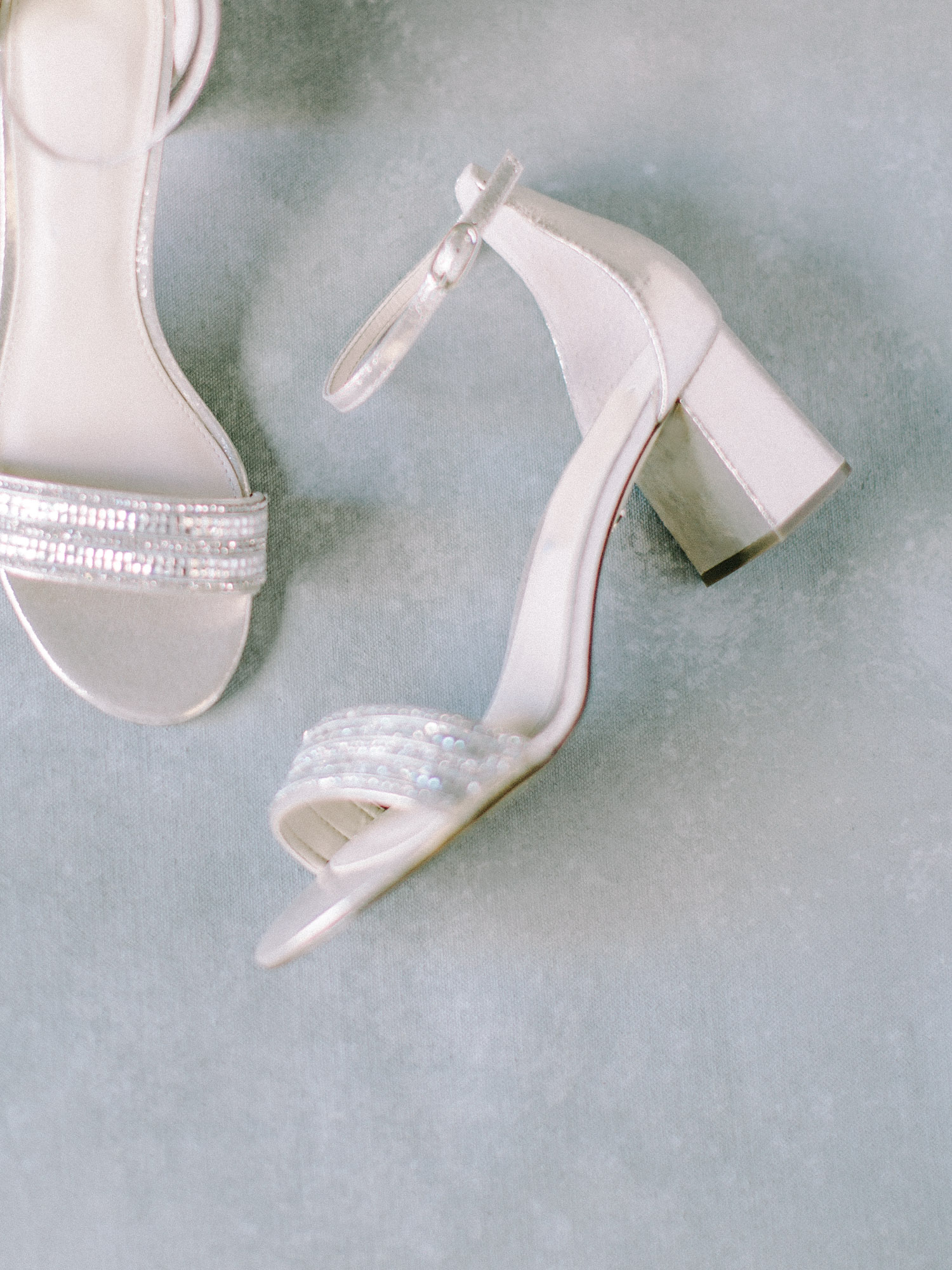 Champagne sparkly wedding shoes rest on a painterly blue background in Ann Arbor, Michigan