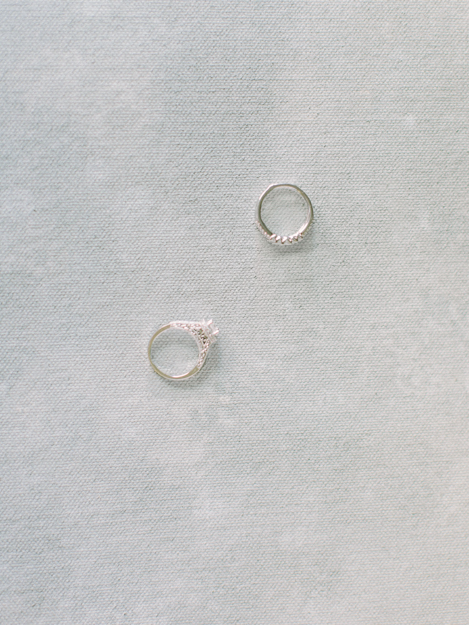 White gold and diamond wedding rings rest on a painterly background by fine art wedding photographer Christina Harrison