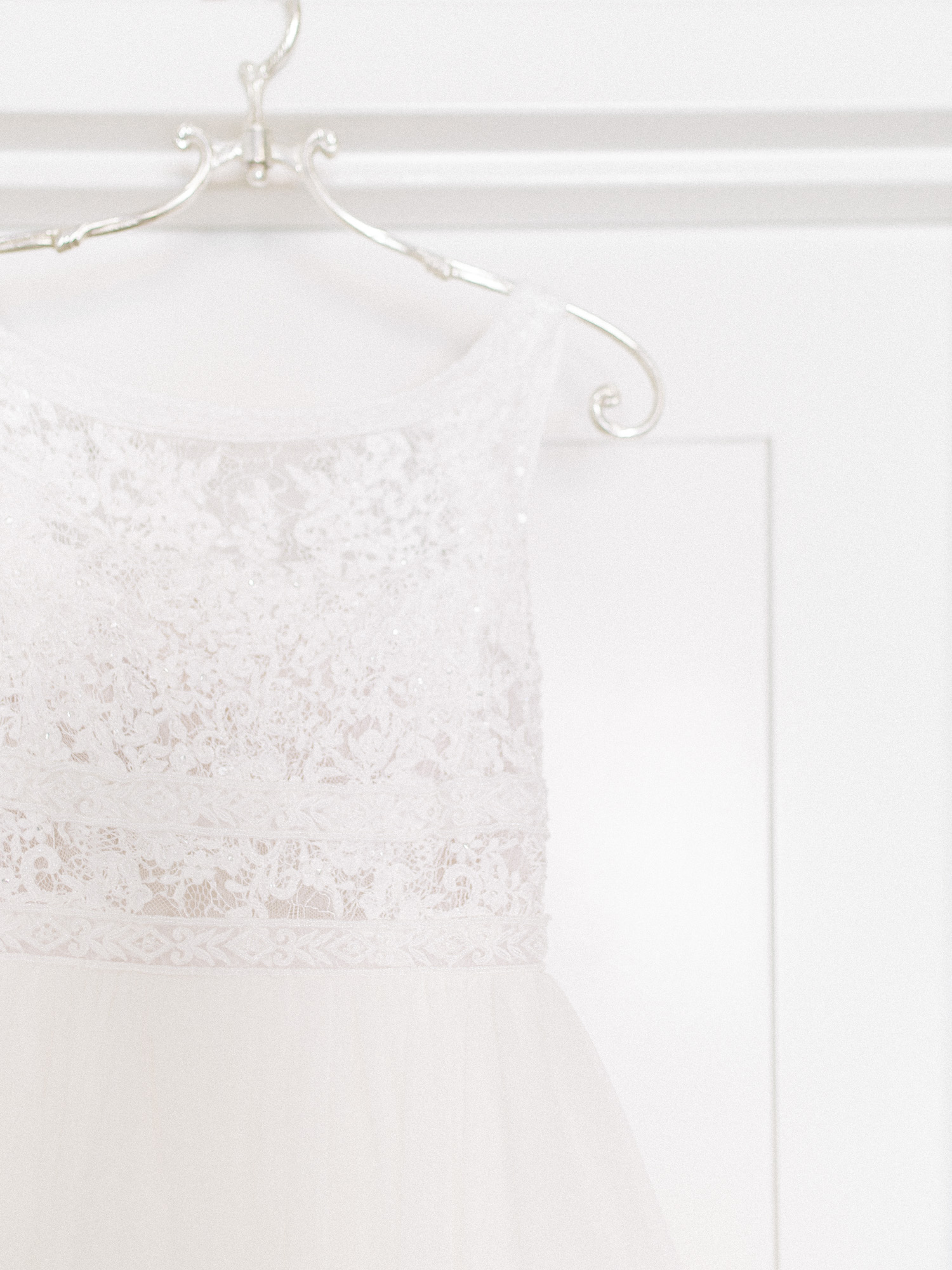 A Rosa Clara wedding gown on a beautiful BHLDN hanger hangs over a white background just before an Ann Arbor wedding