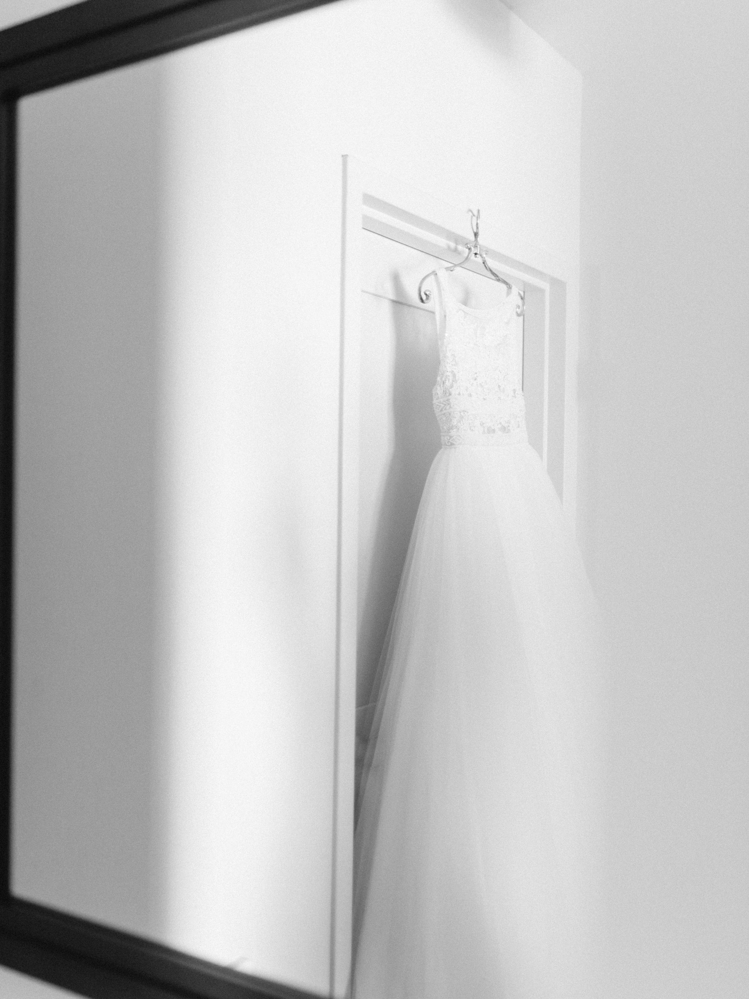 A beautiful Rosa Clara bridal gown with a tulle skirt is reflected in a mirror as it hangs over a door in Ann Arbor, Michigan