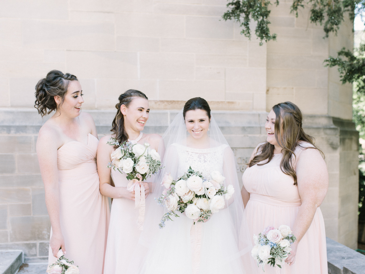 Smiling bridesmaids in blush dresses laugh with the bride outside a church in Ann Arbor, Michigan