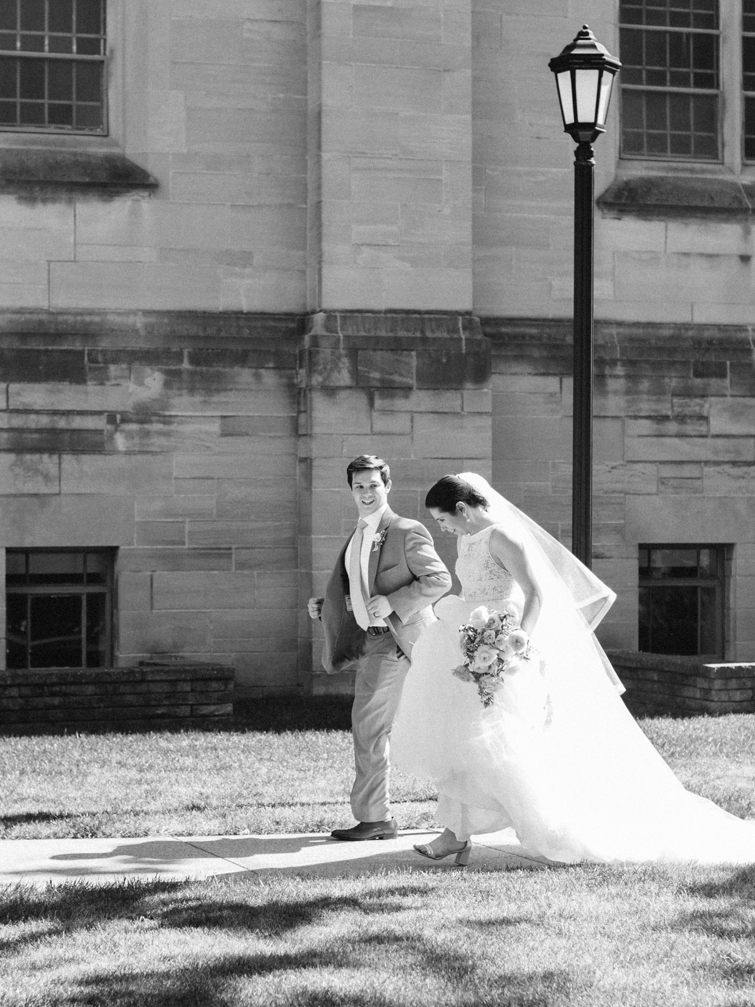 A joyful newlywed couple walks together outside their wedding venue in Ann Arbor, Michigan