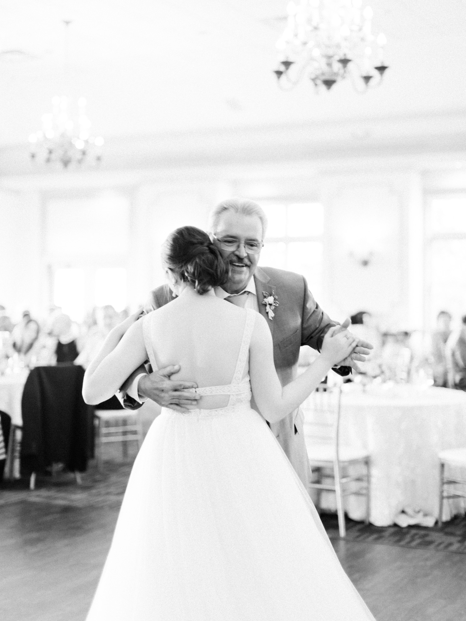 A brides father smiles as he shares a dance with her at The Polo Fields in Ann Arbor