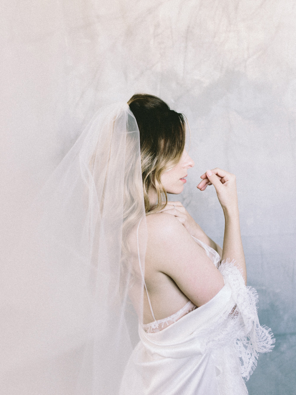 A bride in Girl and A Serious Dream veil and lingerie in a restful pose before dressing for her wedding day