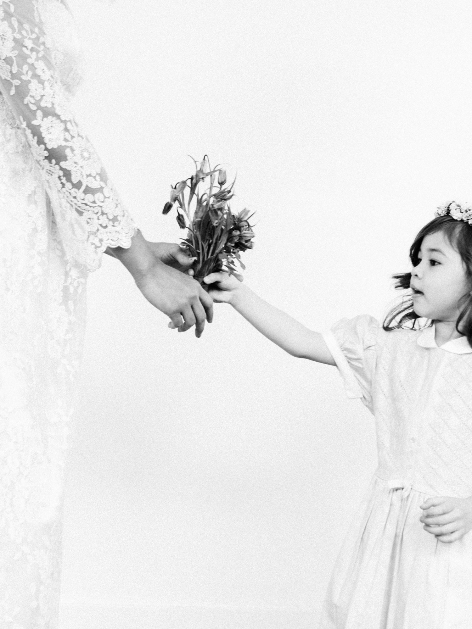 a young flower girl reaches out as a bride in a lace gown hands her a small bouquet