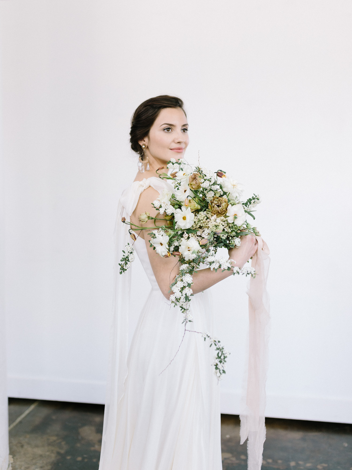 a bride in a clean white space holds an untamed bouquet of foraged spring florals tied with silk ribbon