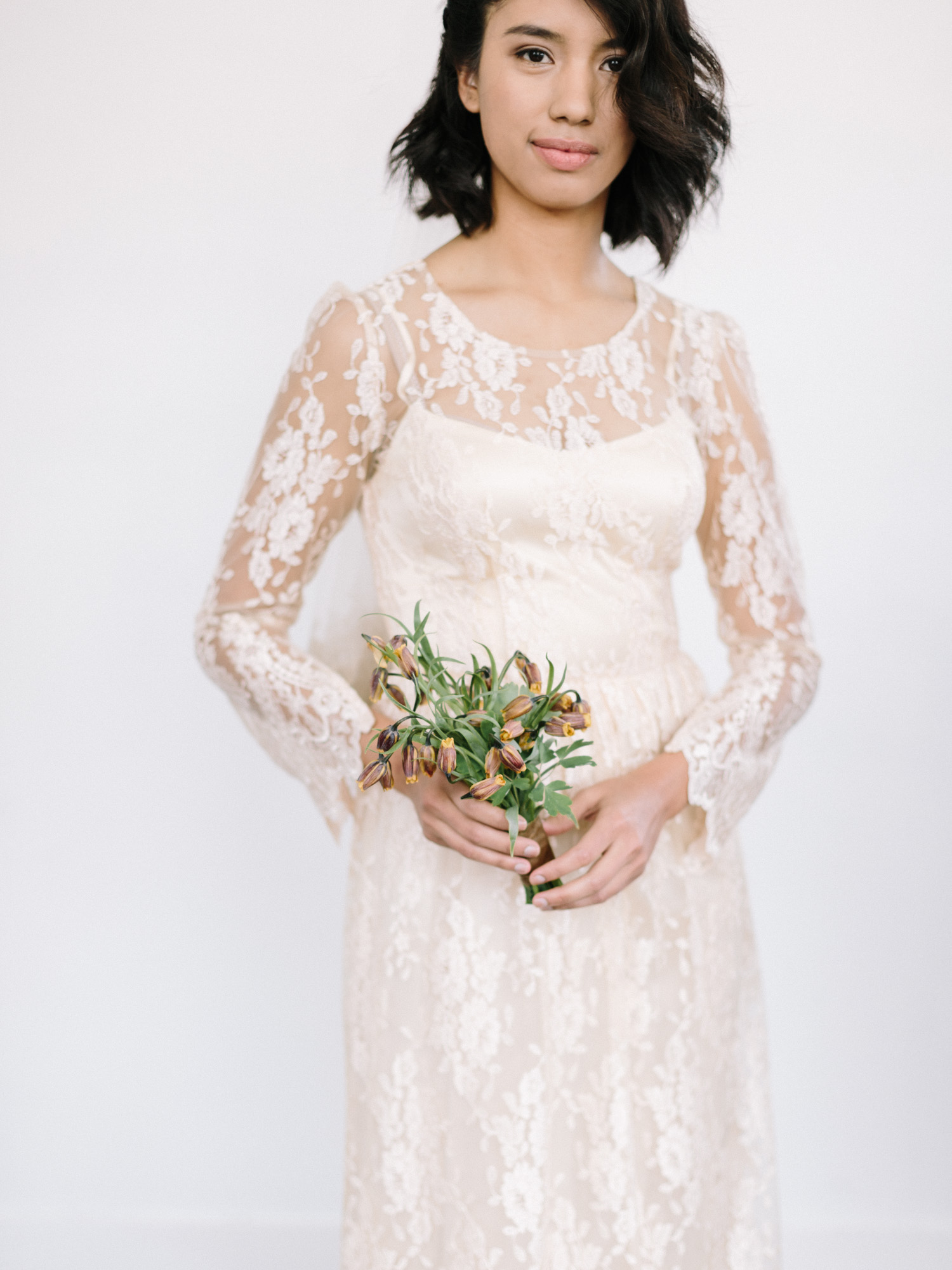 a natural bride in a lace gown holds a small bouquet