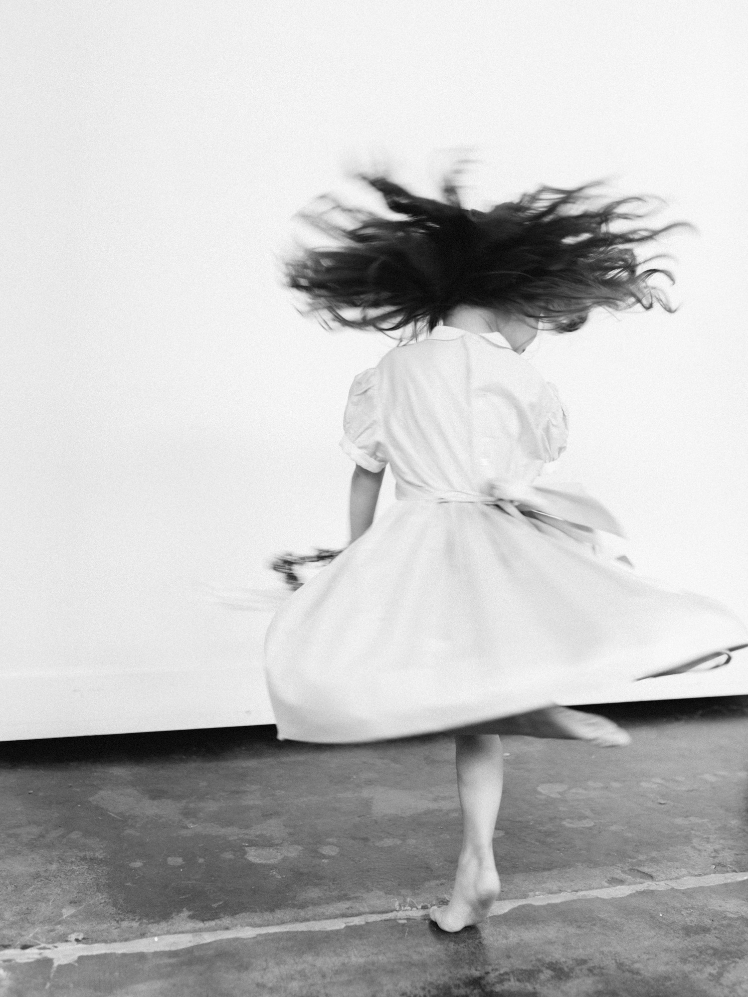 A young flower girl twirls in her dress with bare feet