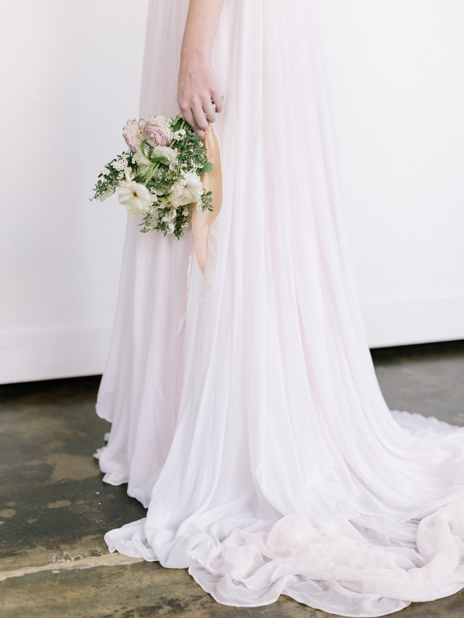 A small bouquet of wild roses and spring flowers is held against a blush silk wedding gown