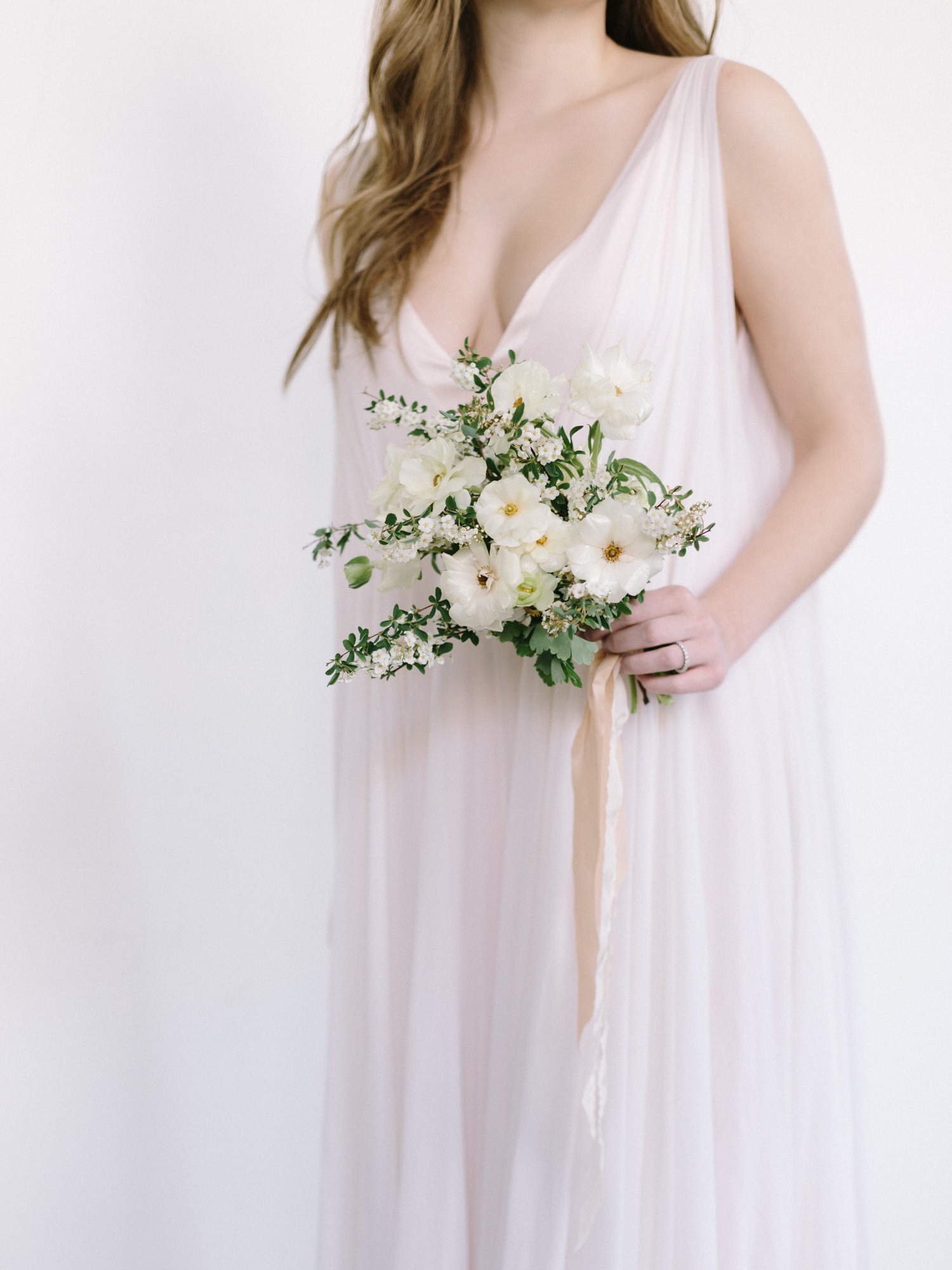 A bride in a blush silk wedding dress holds a small bouquet of spring flowers