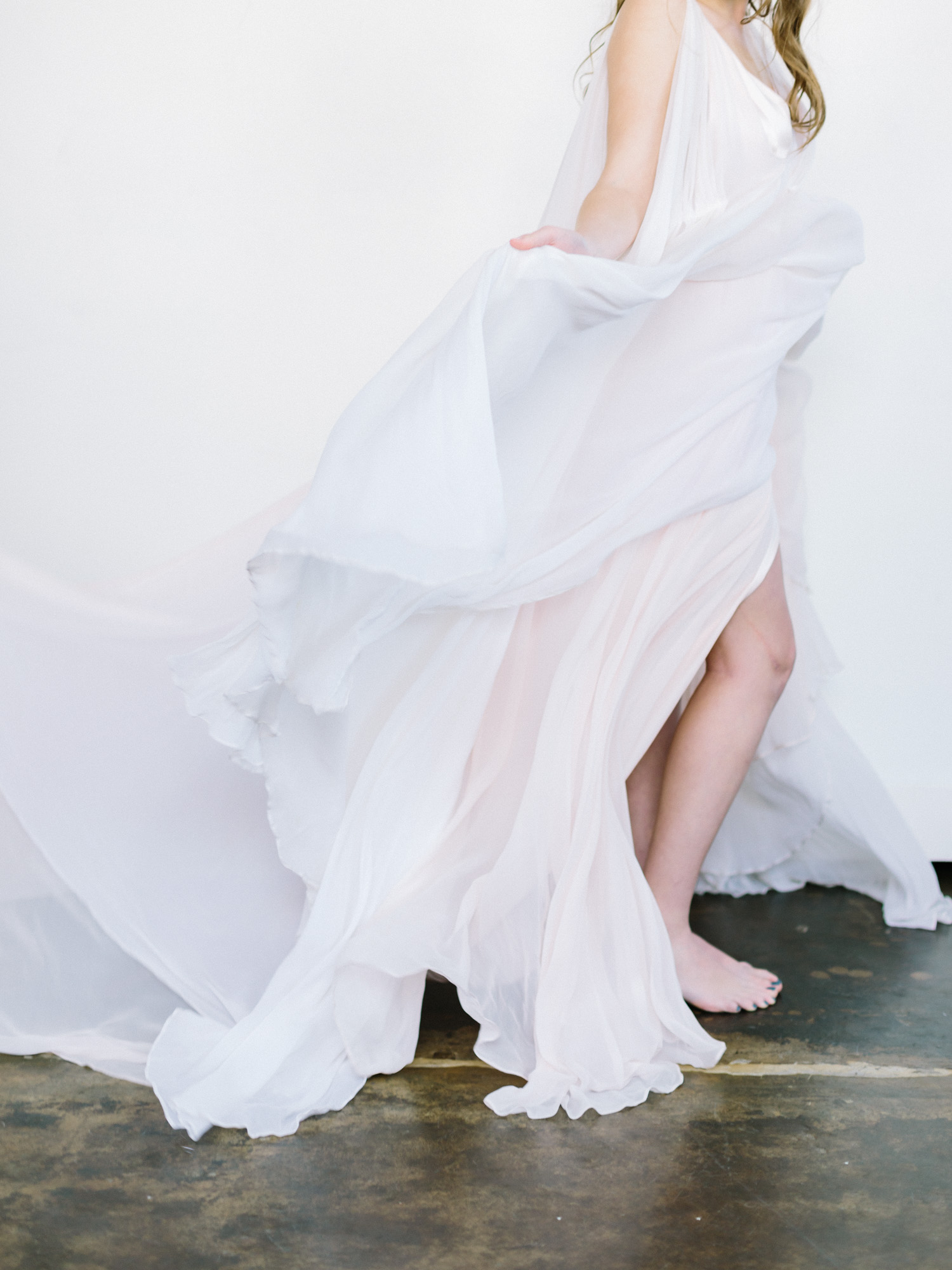 A beautiful Leanne Marshall blush silk wedding gown billows with movement against a white backdrop