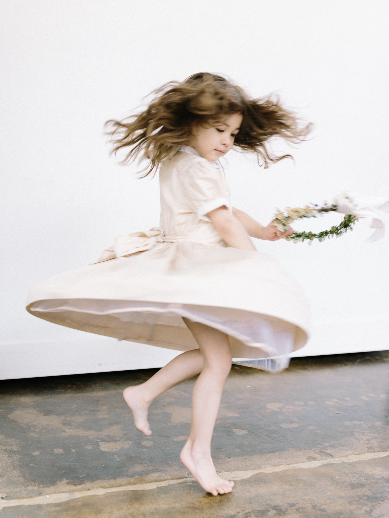 A young flower girl twirls in her dress while holding her spring flower crown
