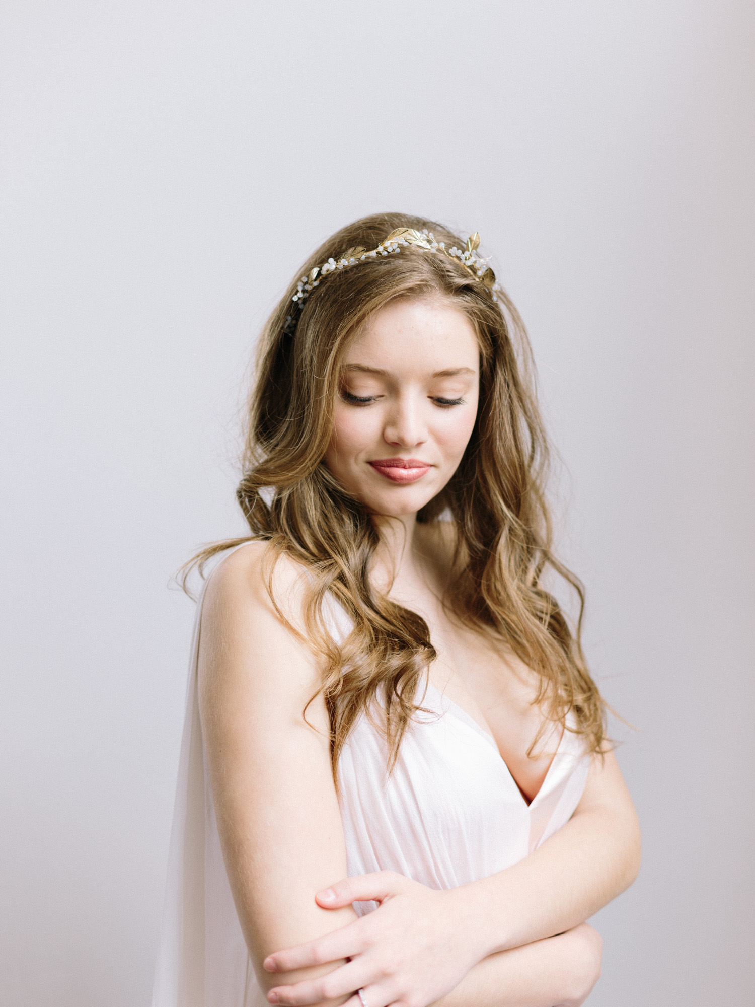a beautiful bride in a blush silk Leanne Marshall wedding gown and gold headpiece smiles serenely with her eyes closed