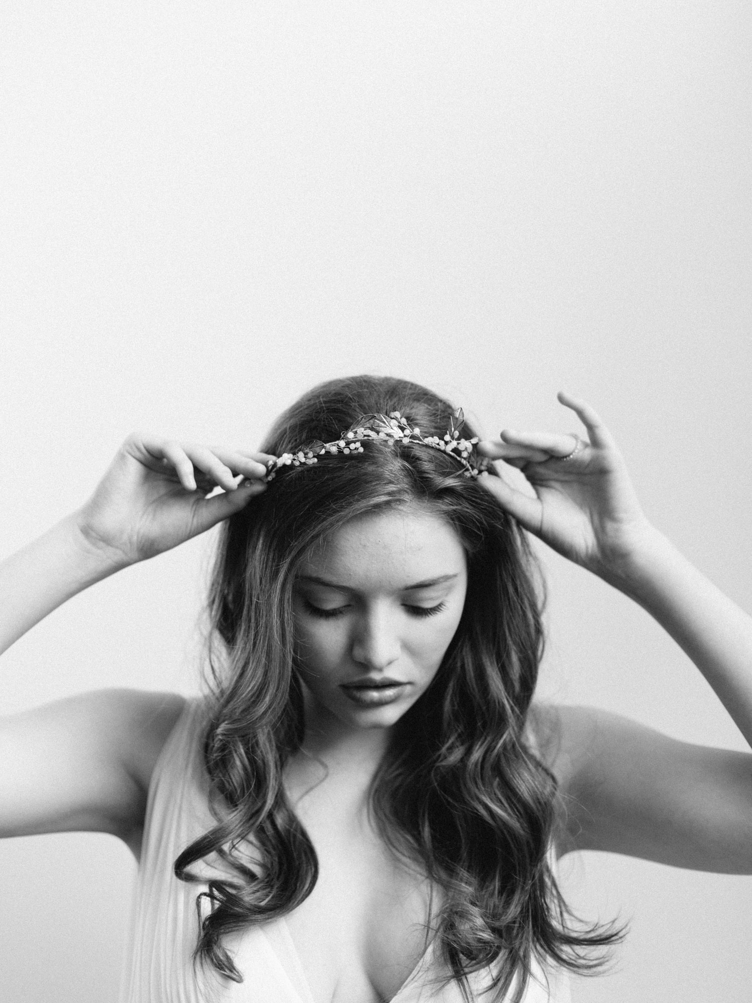 a bride with her hair down and curled looks down as she places a vine headpiece on her head