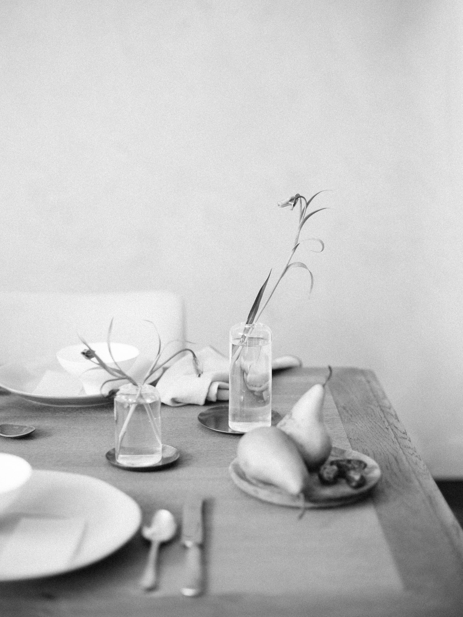 vases with minimal greenery and a plate of pears and figs rest on a wood table