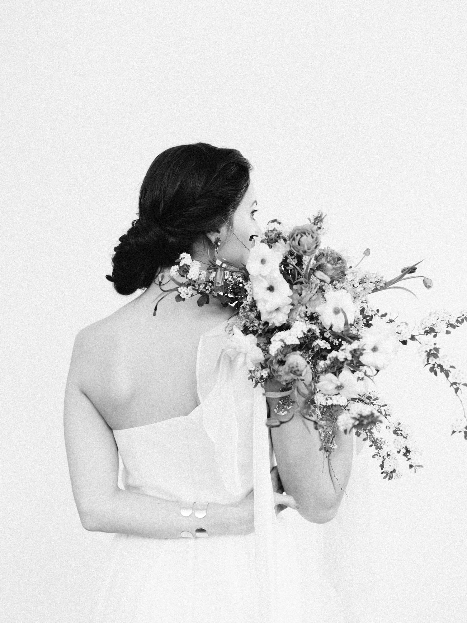 A bride holds an untamed bouquet of foraged spring flowers over her shoulder