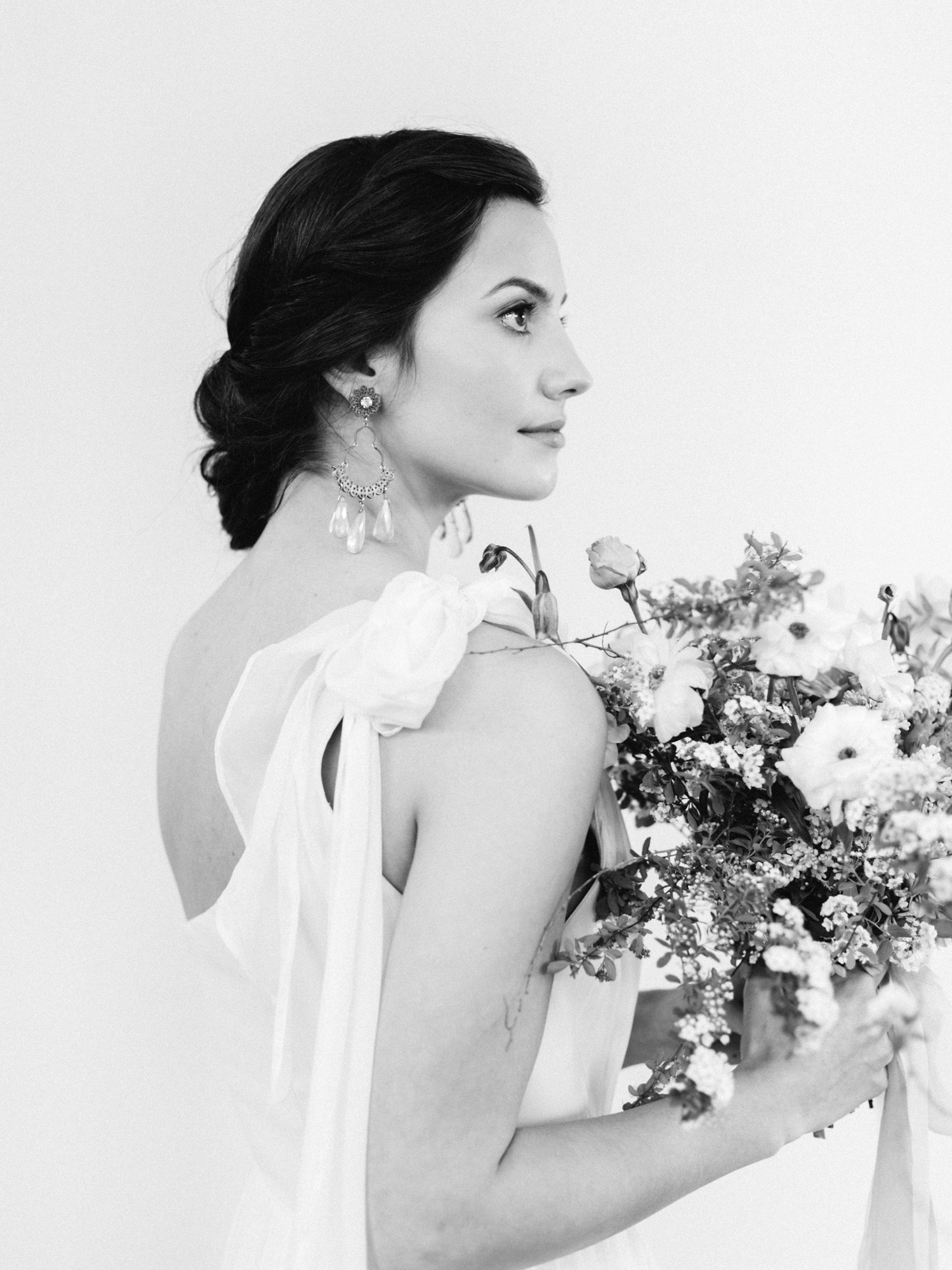 Detail of a bride in a one-shoulder silk Leanne Marshall wedding gown and crystal earrings, holding a bouquet of flowers