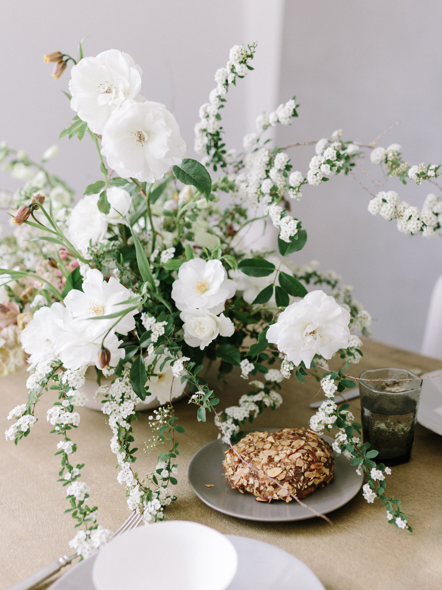A wild, untamed floral centerpiece with white garden roses and flowering branches rests on a wood table