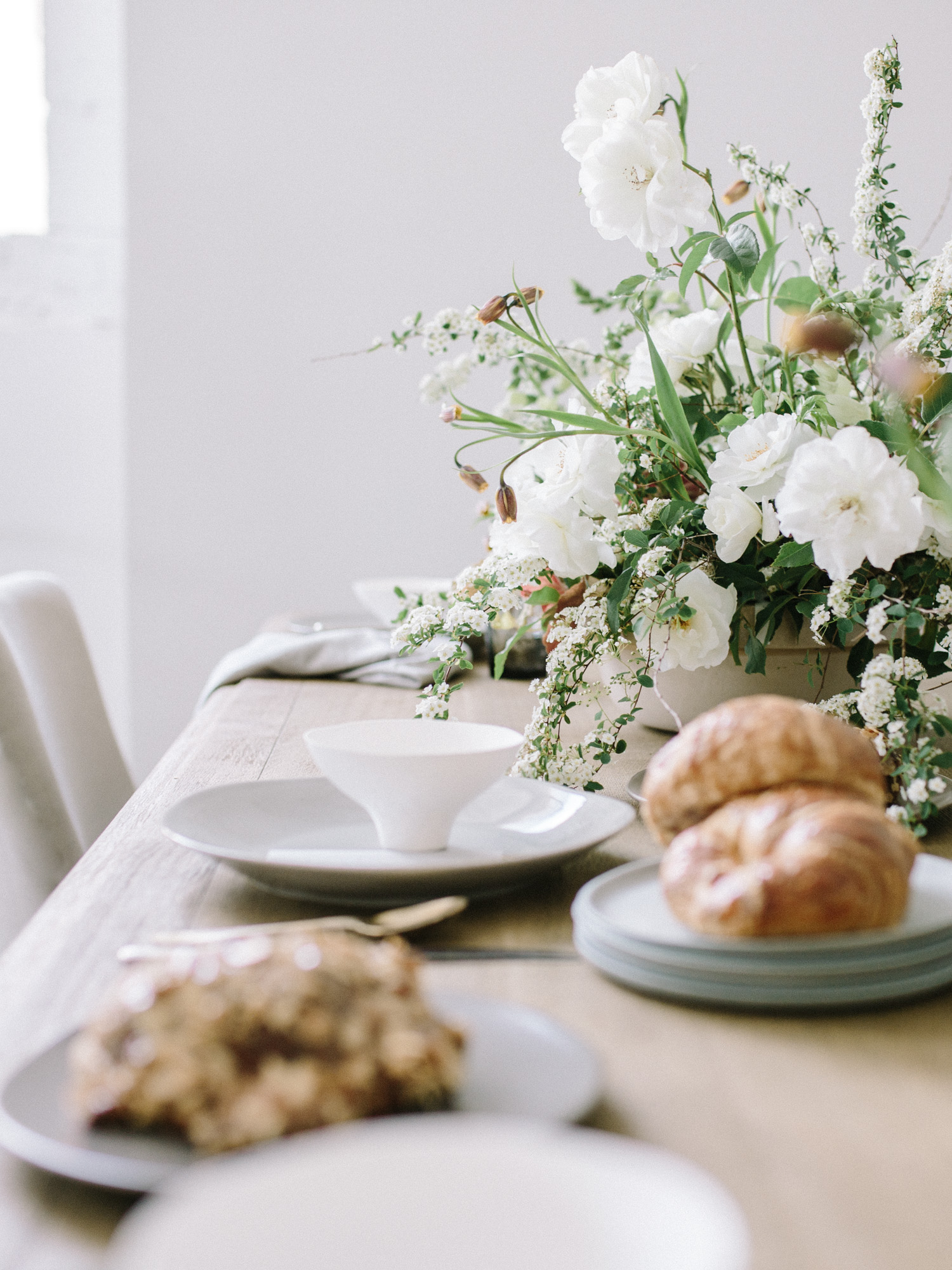 Bowls, plates, croissants, and a spring floral centerpiece rest on a table