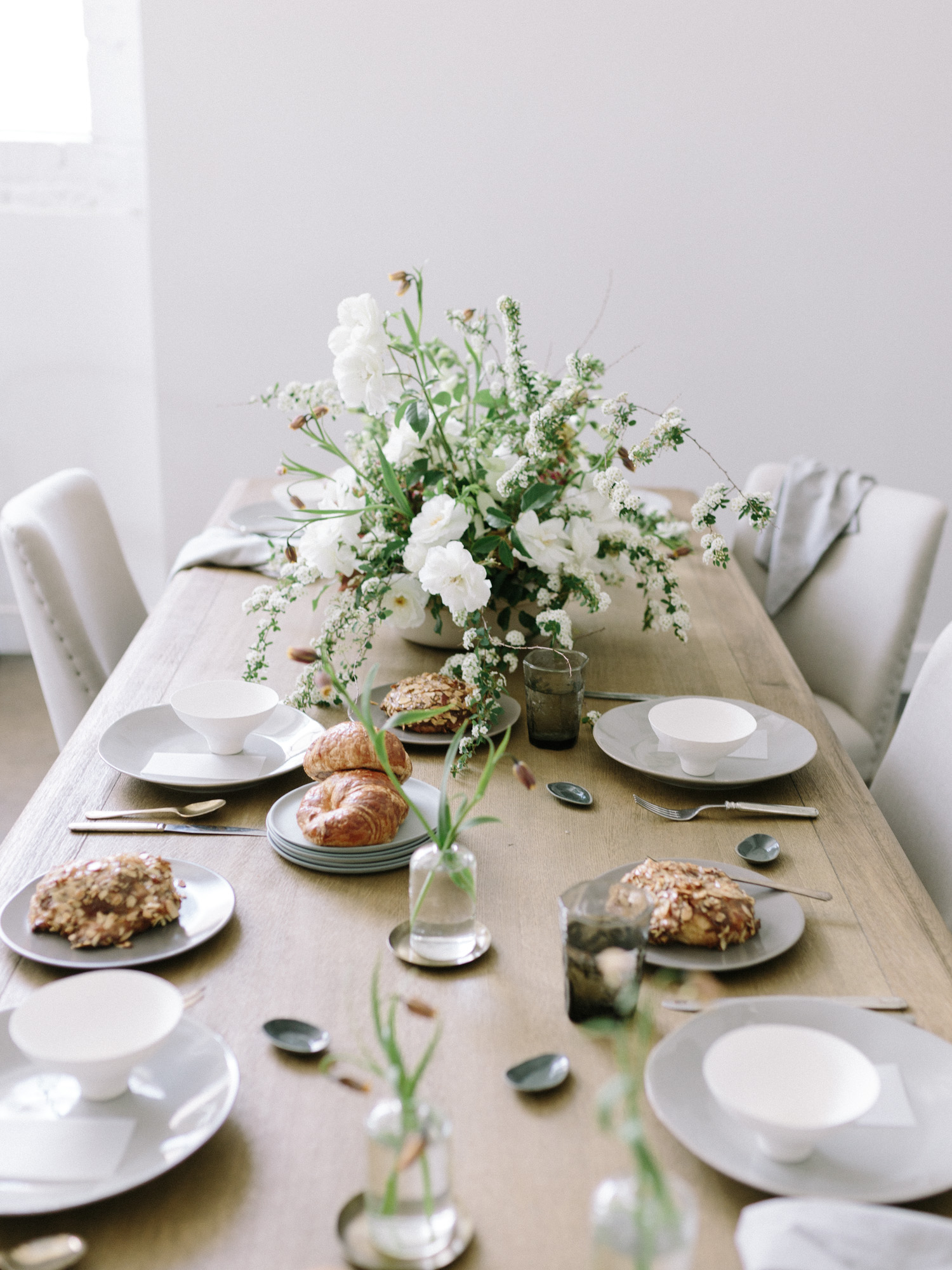 a fresh spring table scape with croissants and an untamed floral centerpiece