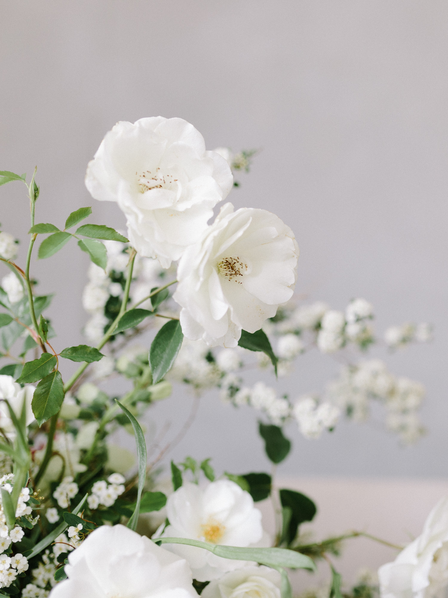 Foraged white garden roses in an untamed spring wedding centerpiece