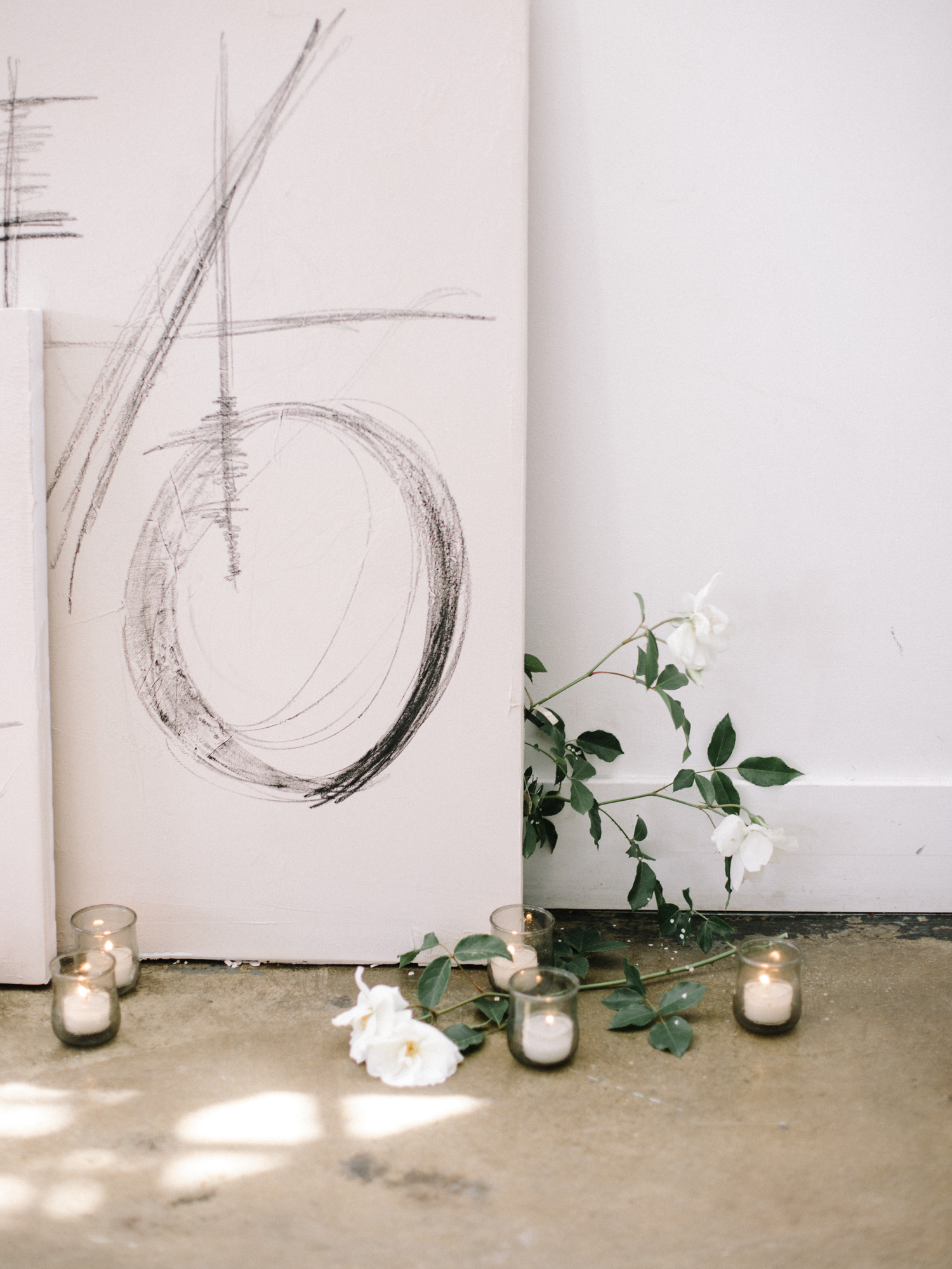 Gestural artwork rests against a wall with white garden roses and tea light candles