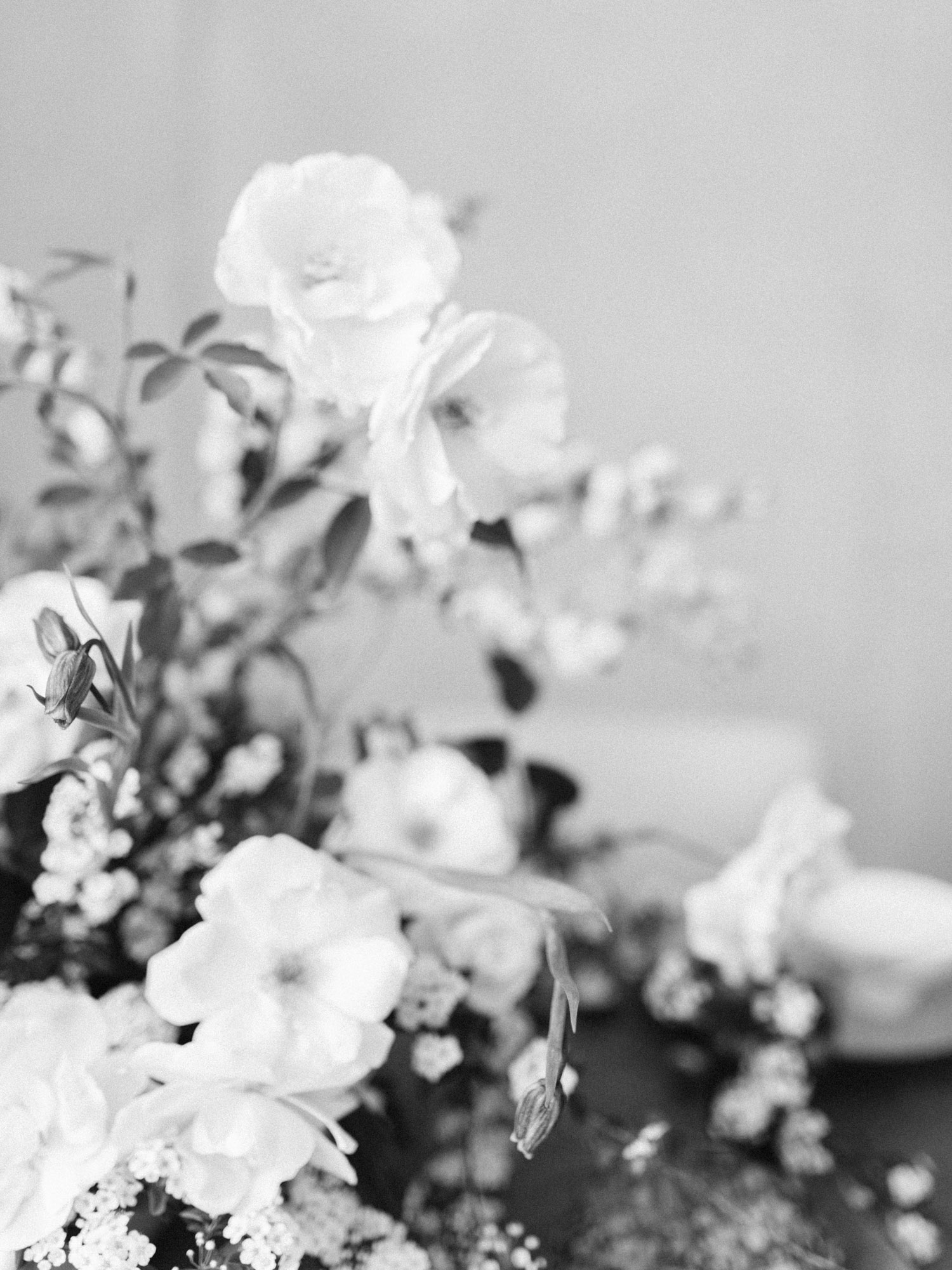 Black and white detail of white garden roses in an untamed floral centerpiece