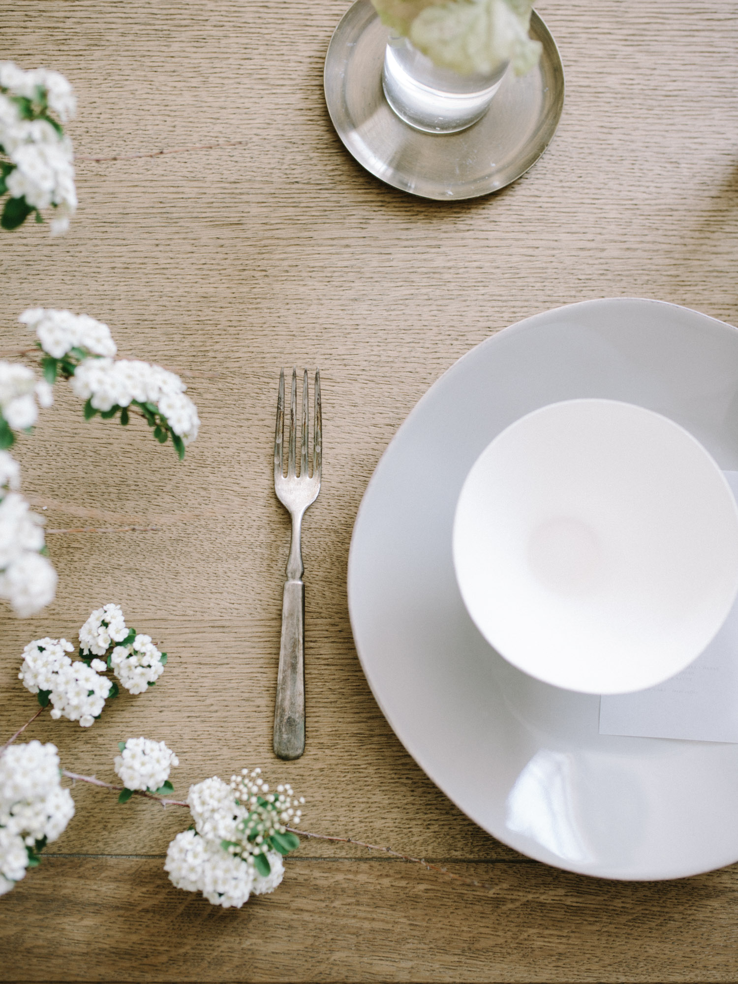 white flowering branches encroach upon a setting at a wood table; a vintage fork with beautiful patina, and a white bowl sitting atop a blue plate.