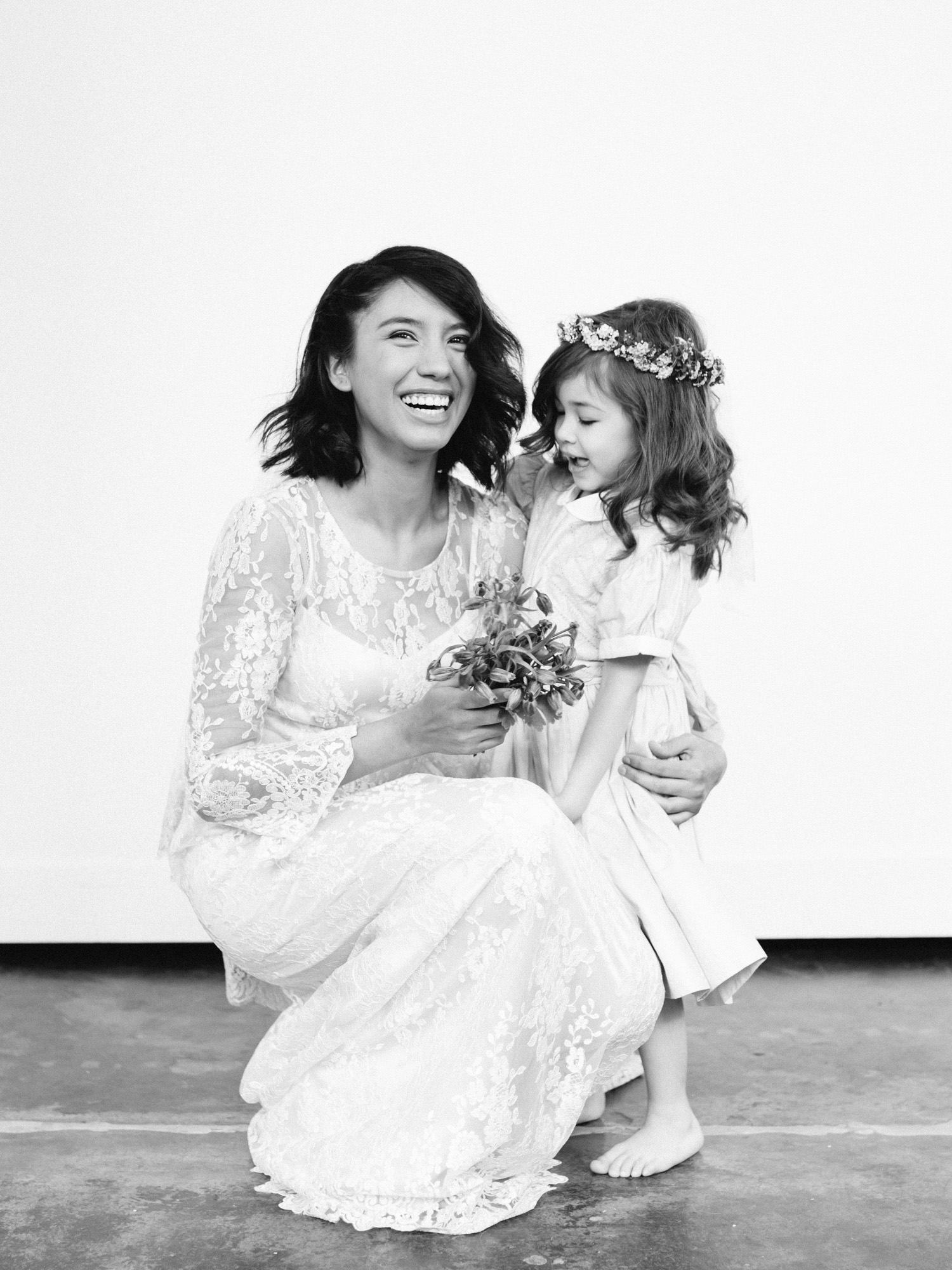 a bride in a lace gown and her flower girl laugh together