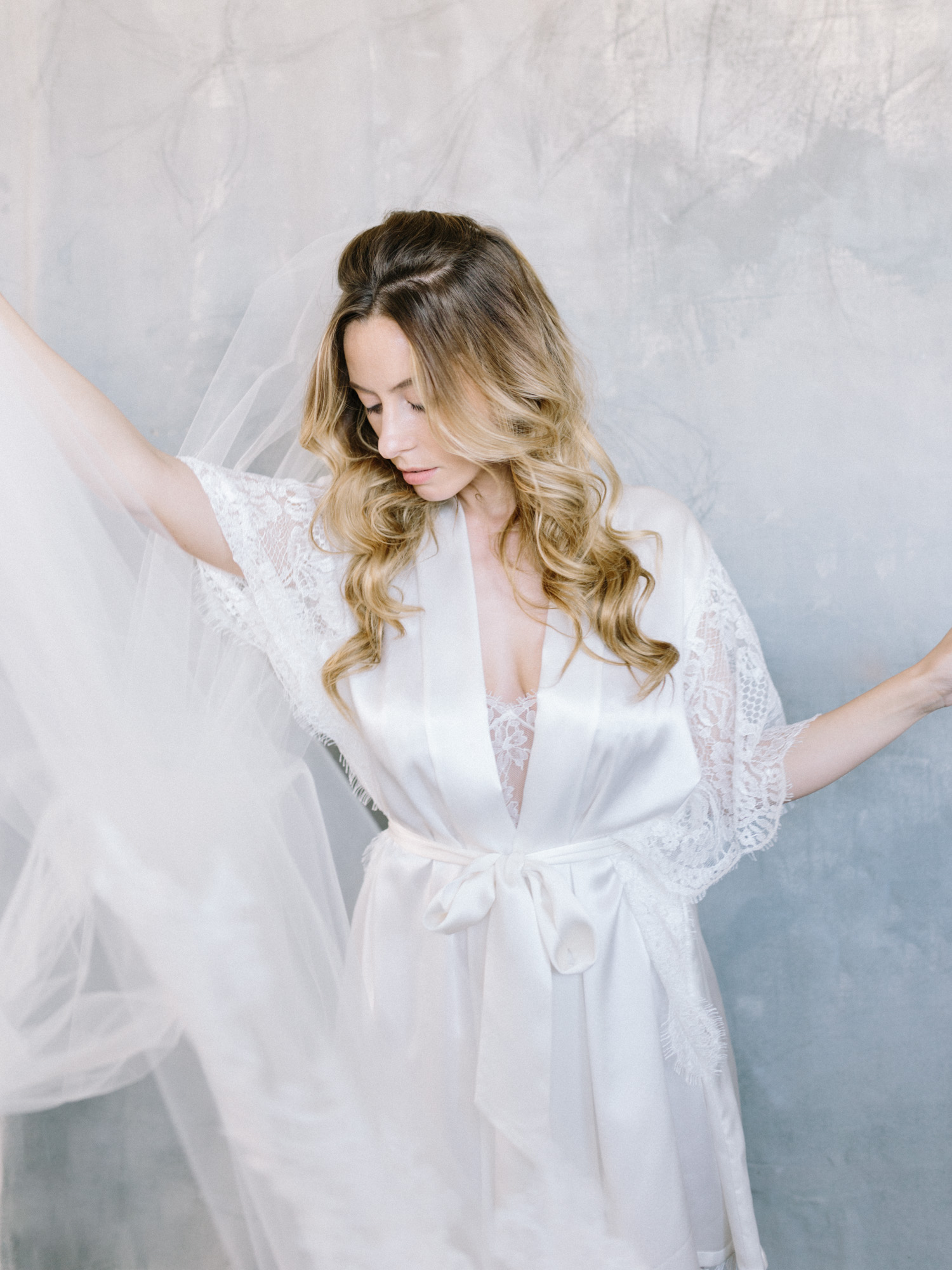 a bride in a Girl And A Serious Dream white lace robe creates movement with her long cathedral veil against a painterly blue backdrop