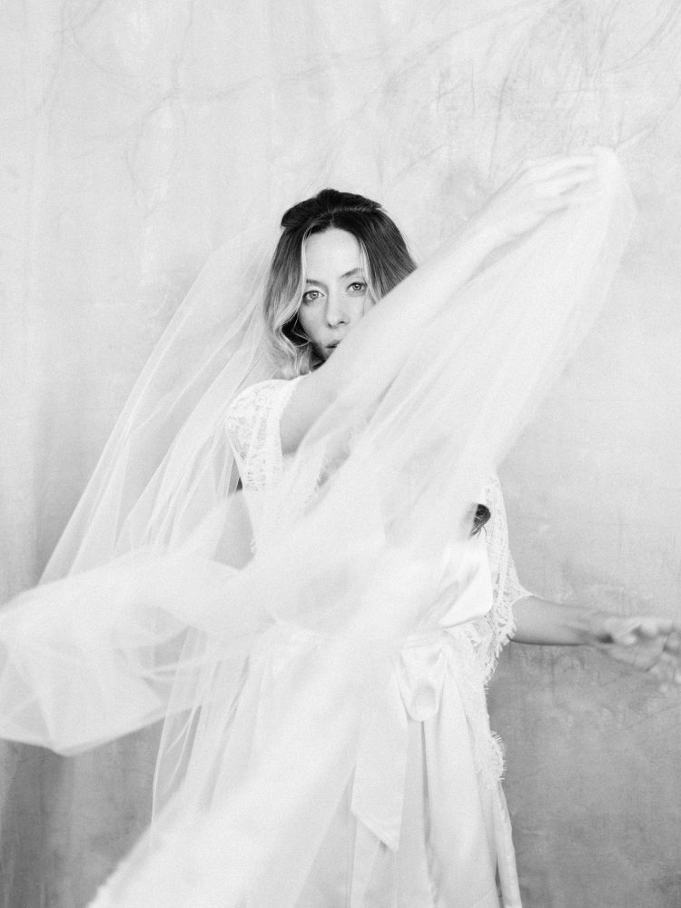 a bride in a white lace robe looks at the camera while creating dynamic movement with her long cathedral length veil, captured by Christina Harrison Photography