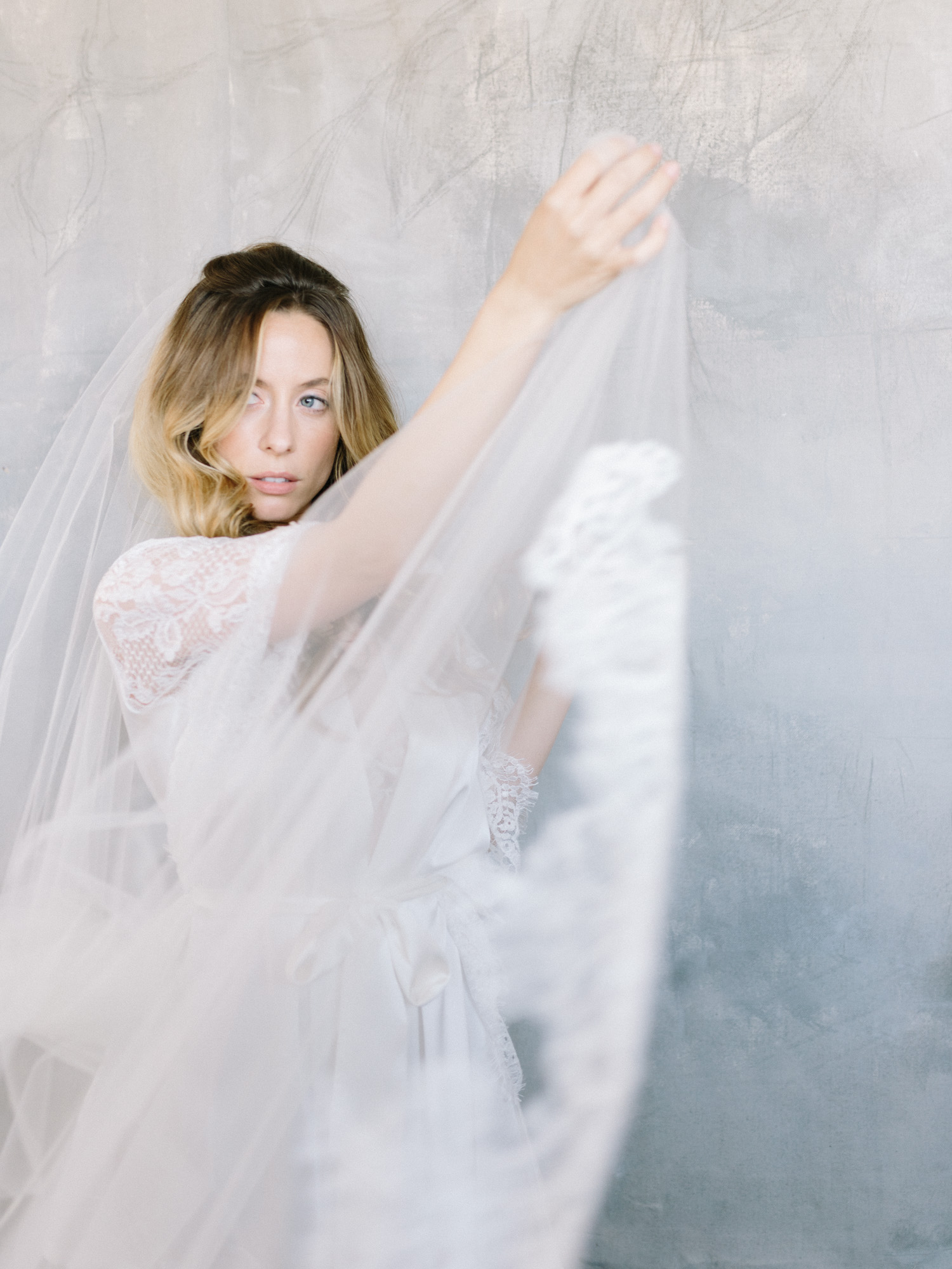 A bride wearing a Girl and A Serious Dream cathedral veil and white lace robe adjusts her veil