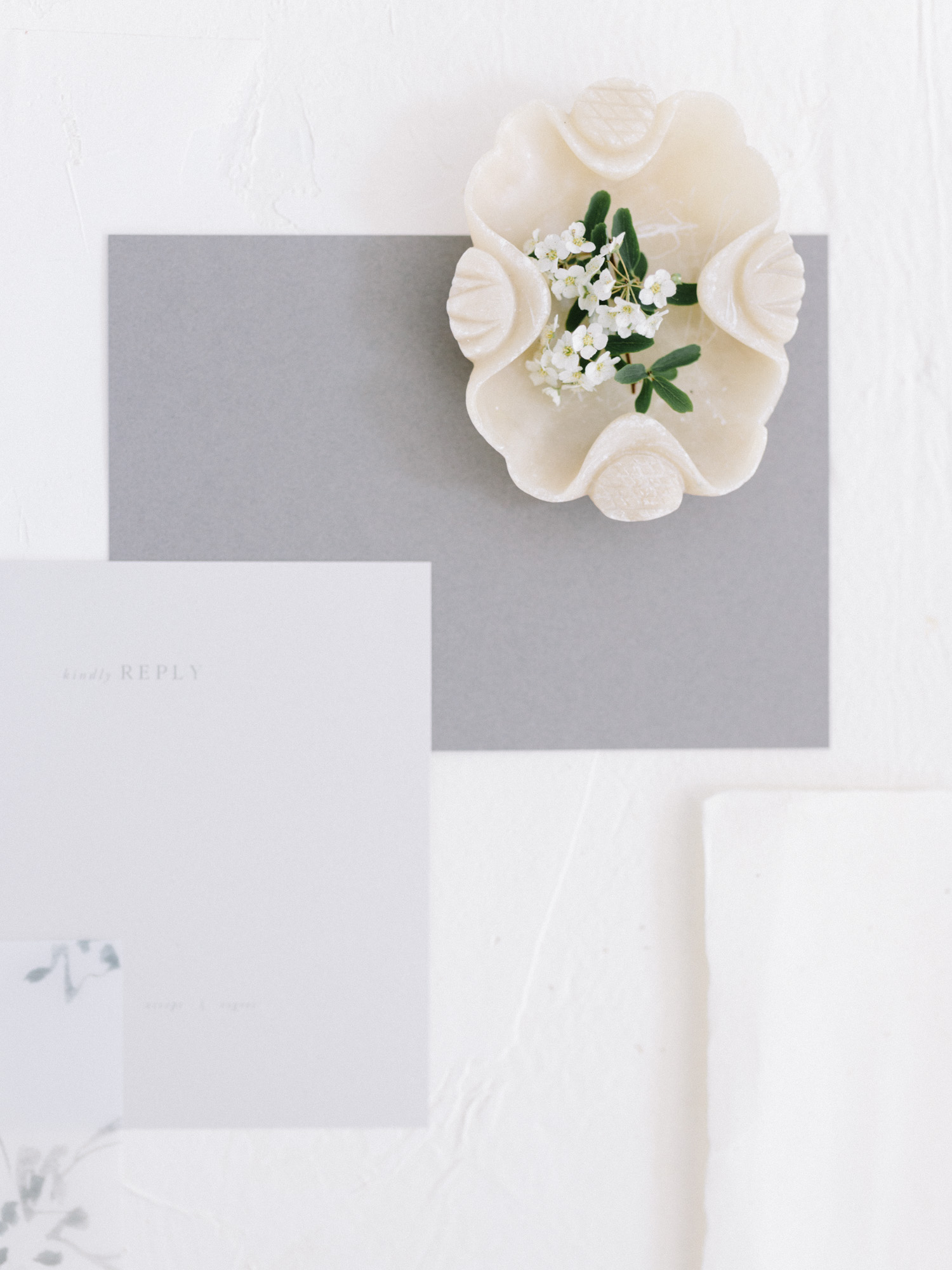 Minimal wedding invitations in shades of grey rest against a white background, along with a dish of tiny flowers