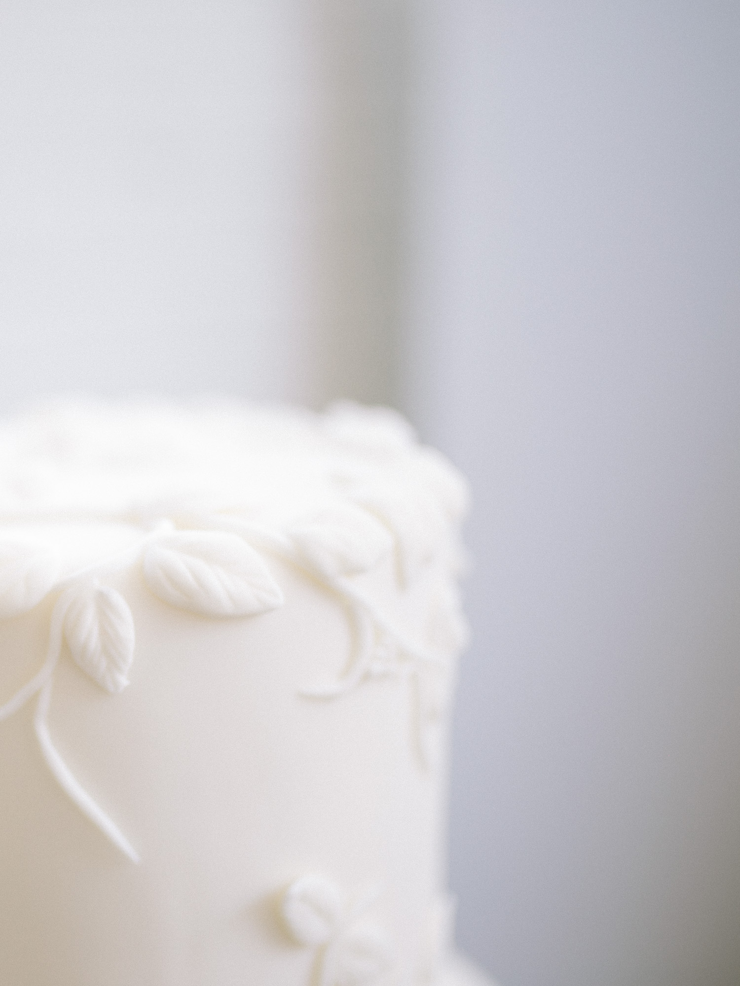 Vines and leaves sculpted in fondant on a white wedding cake are shown in detail