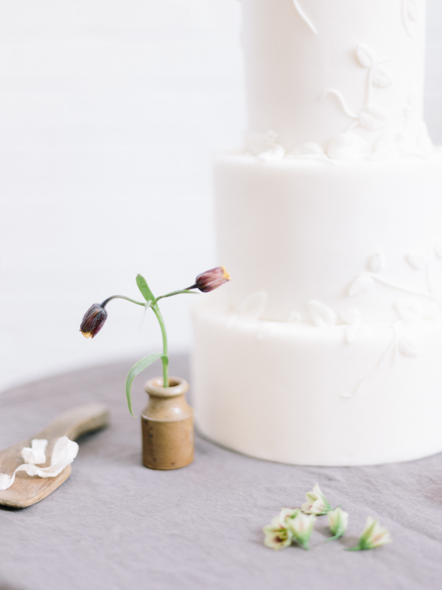 A handmade ceramic vase with a flower serves as wedding cake table decor