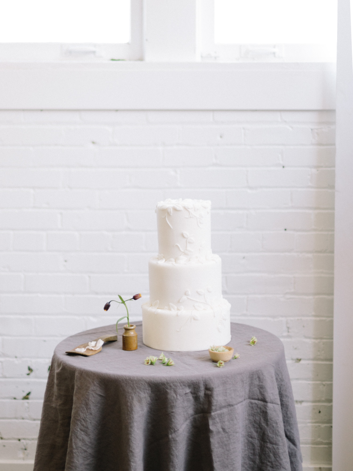 A three tier white wedding cake with vine design rests on a table with flowers