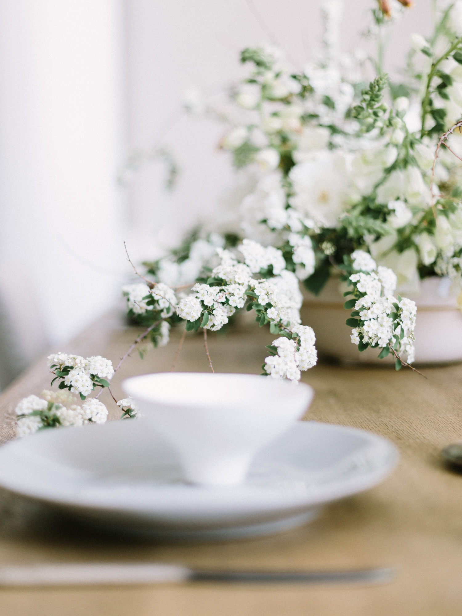 Flowering branches in an untamed spring centerpiece reach toward a place setting at a wedding in Salt Lake City