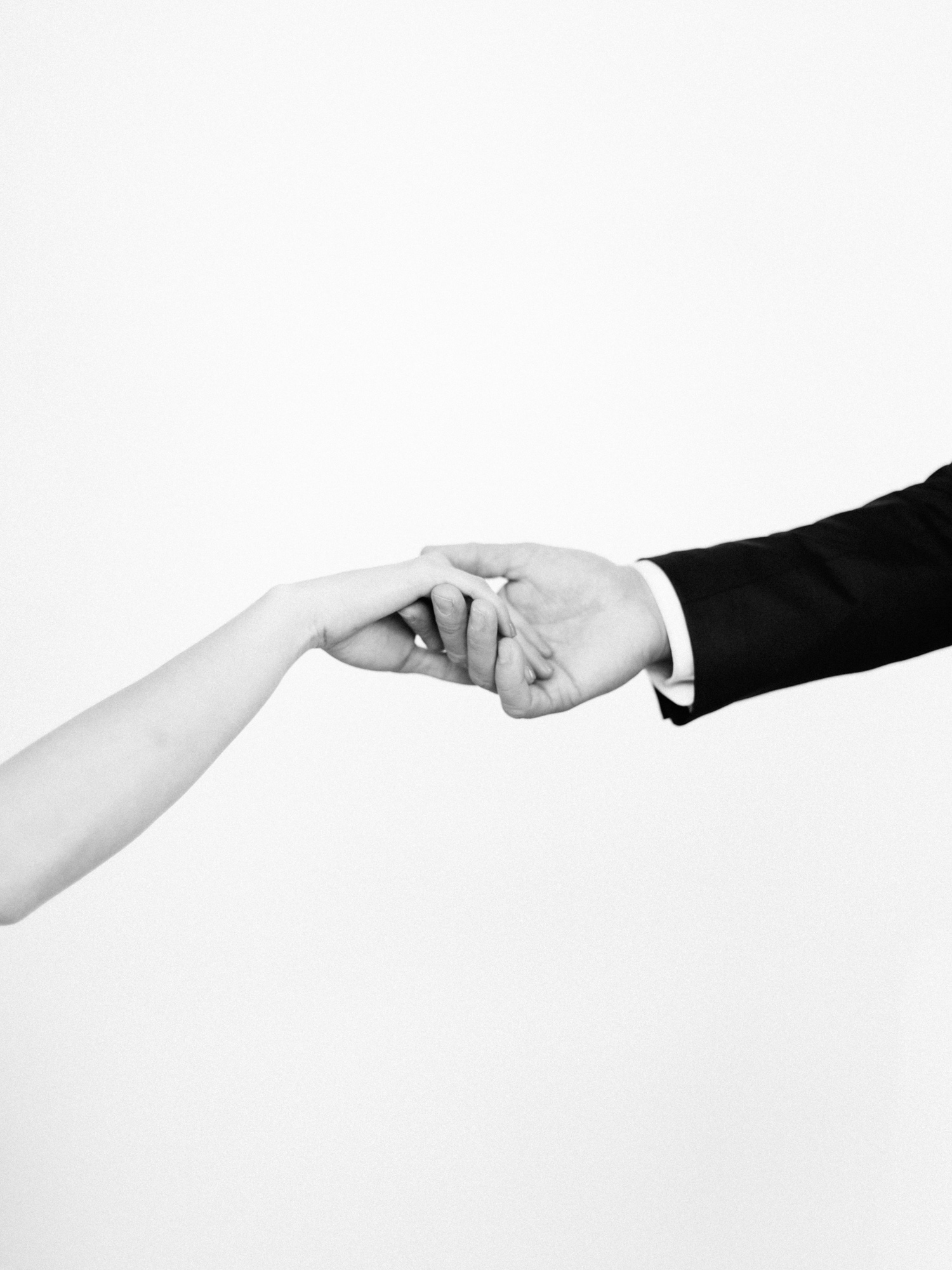 a simple photo of a woman's hand in a man's hand against a white background