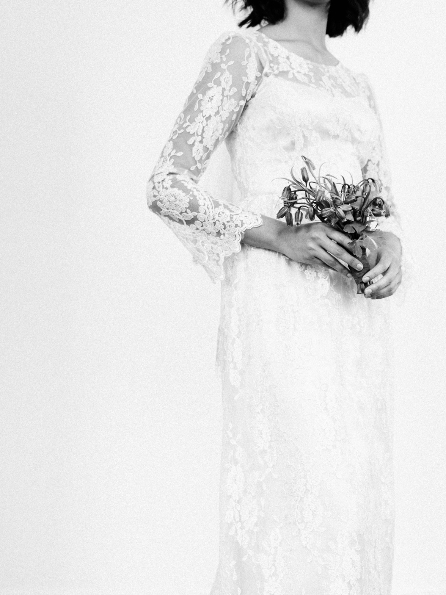 Detail of a wedding gown with full lace sleeves is shown as a dark-skinned bride holds a small bouquet of flowers