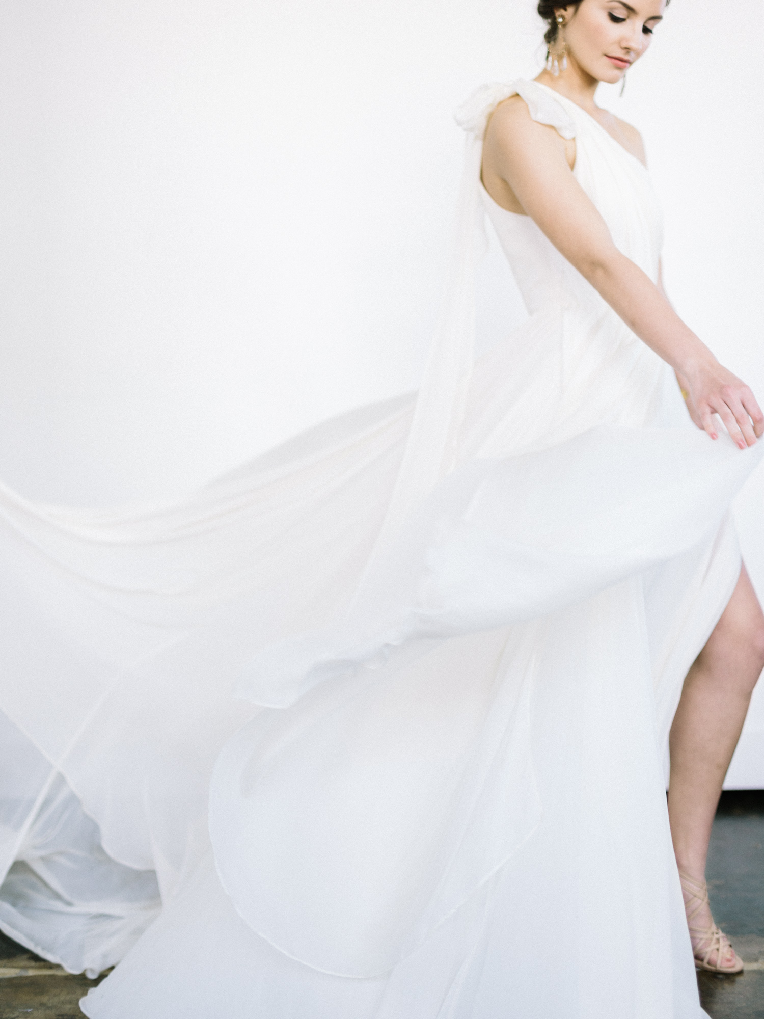 A bride against a white background creates movement with the billowing silk layers of her Leanne Marshall gown