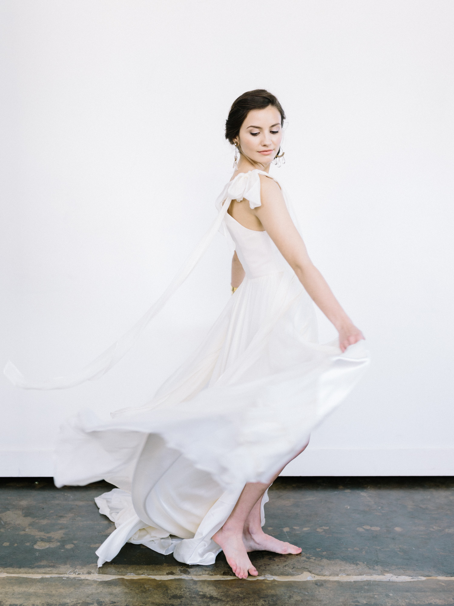 a bride in a silk Leanne Marshall gown twirls to create billowing movement of fabric