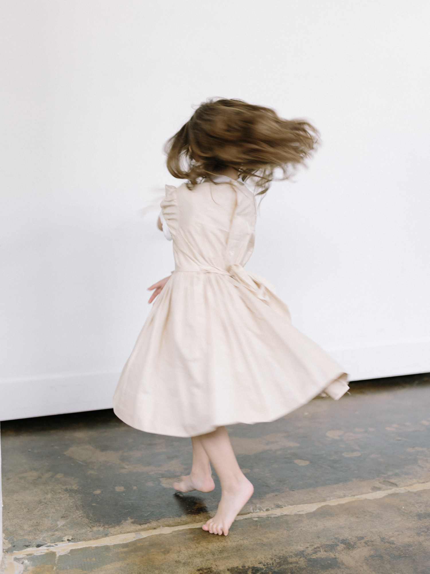motion blur is captured as a young flower girl twirls with bare feet