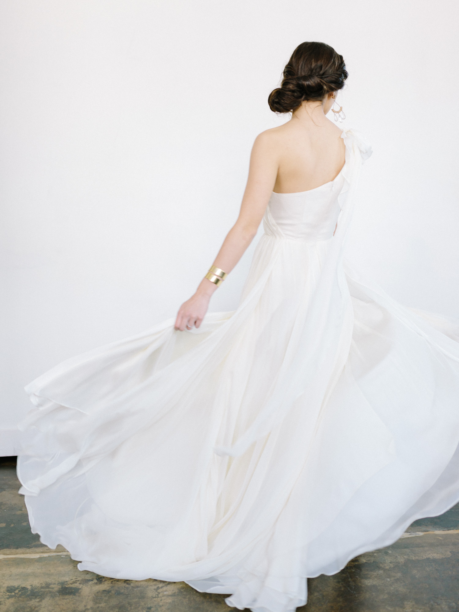 A bride in a modern white venue space twirls in her silk Leanne Marshall gown