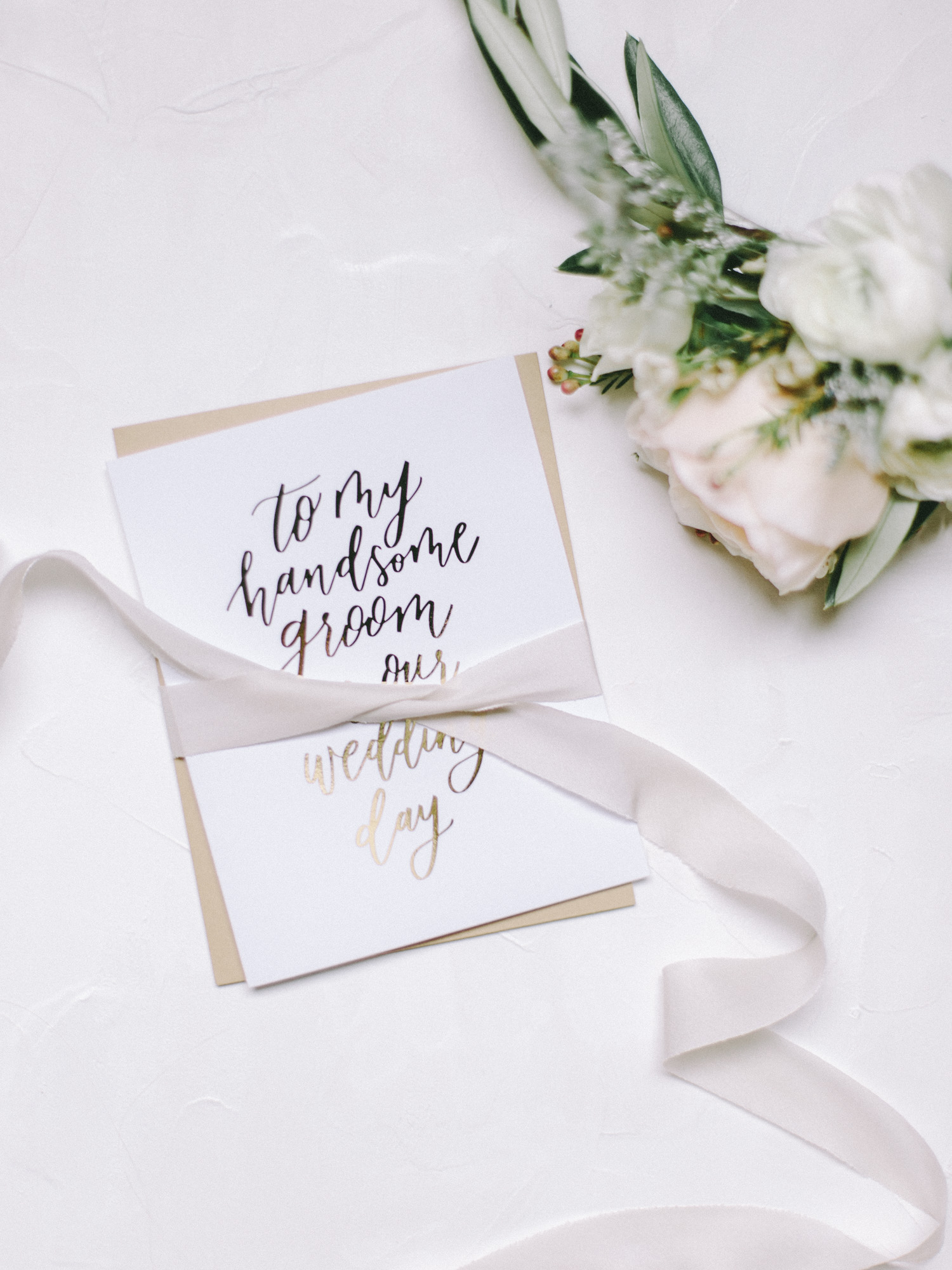 A card from the bride to her groom on their wedding day, wrapped in ribbon resting on a white background