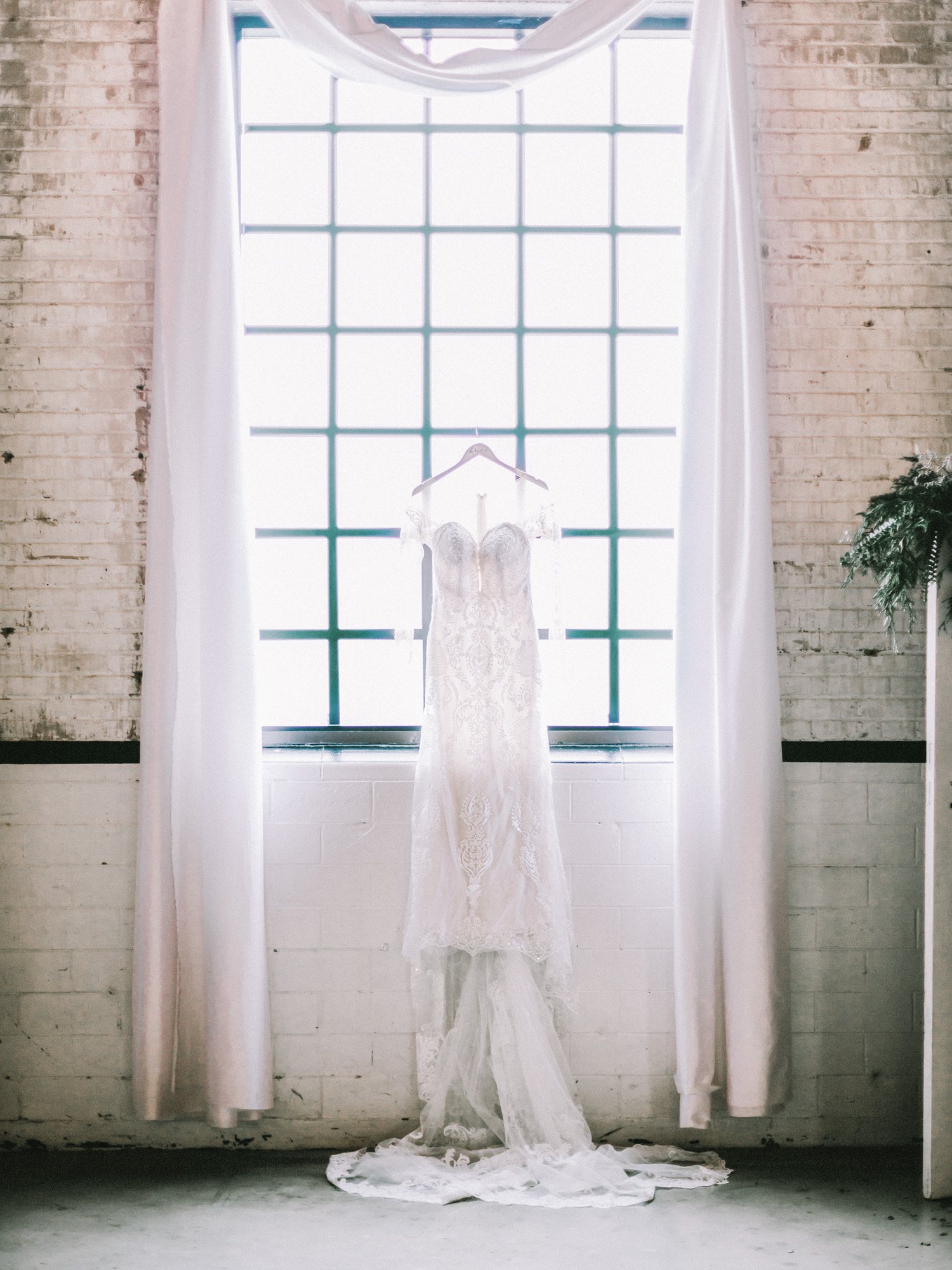 A detailed ethereal lace wedding dress hangs in the window of The Brick, an industrial wedding venue in South Bend near Michigan