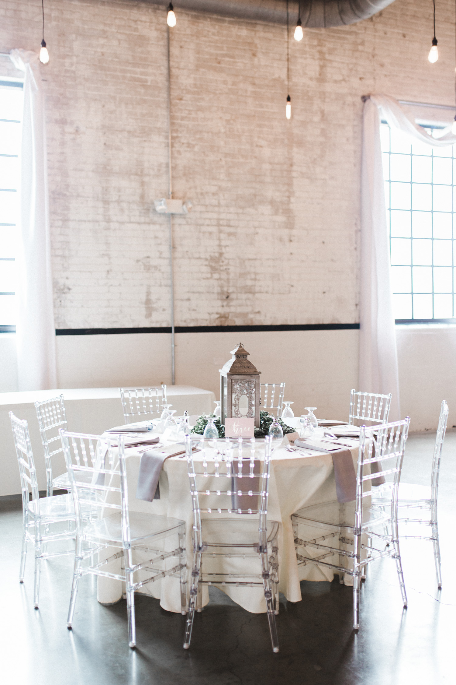 ethereal white and blush reception table setup in an industrial space with clear chiavari chairs, lantern, and greenery at The Brick wedding venue by wedding photographer Christina Harrison