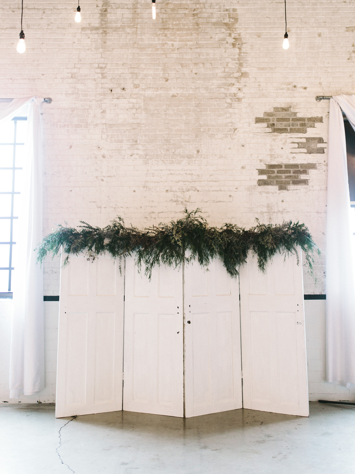 White doors topped with lush greenery serve as a unique wedding ceremony backdrop at The Brick in South Bend