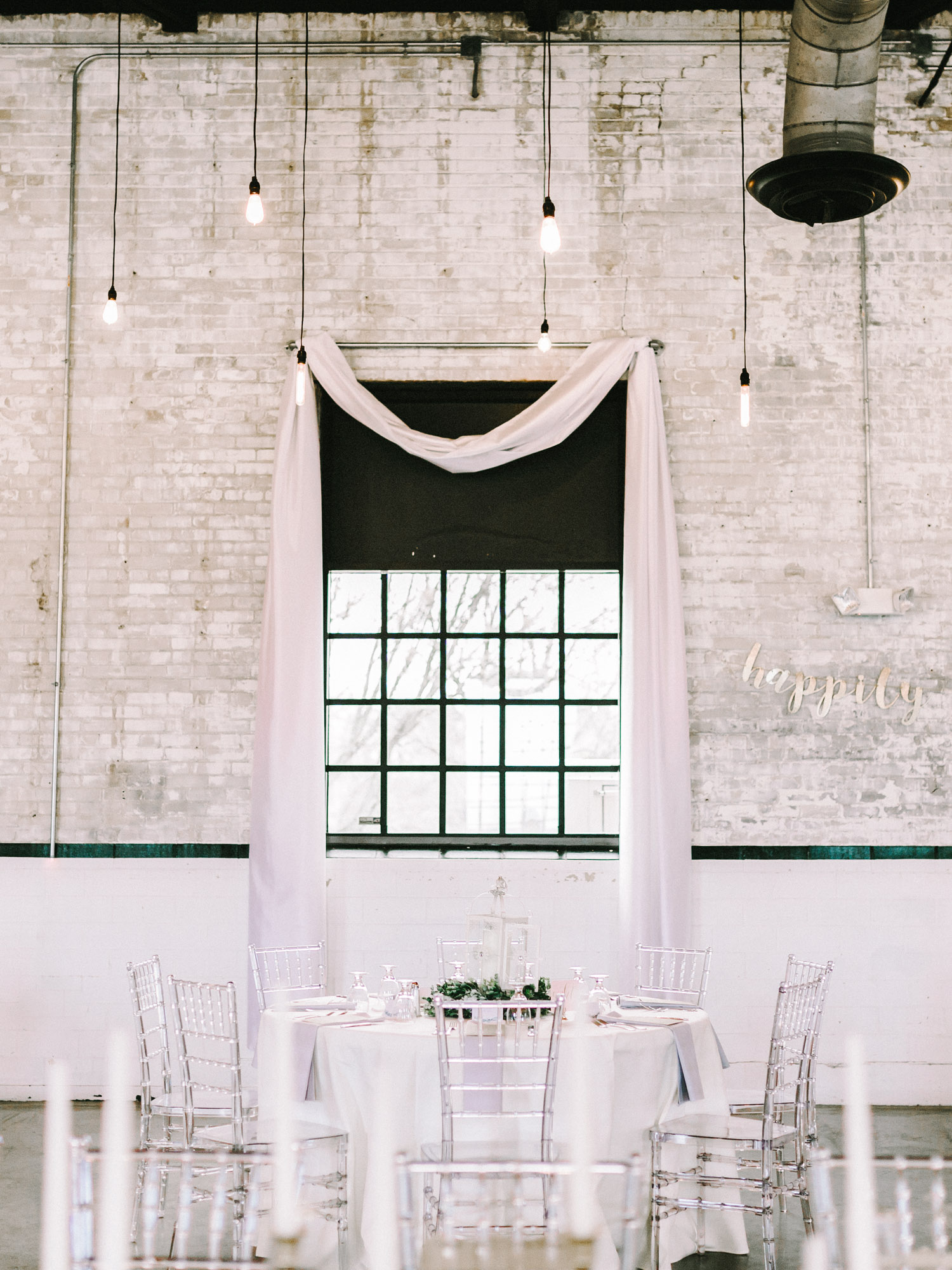 White and blush reception table setup at The Brick, an industrial South Bend wedding venue with hanging Edison bulbs and light colored brick