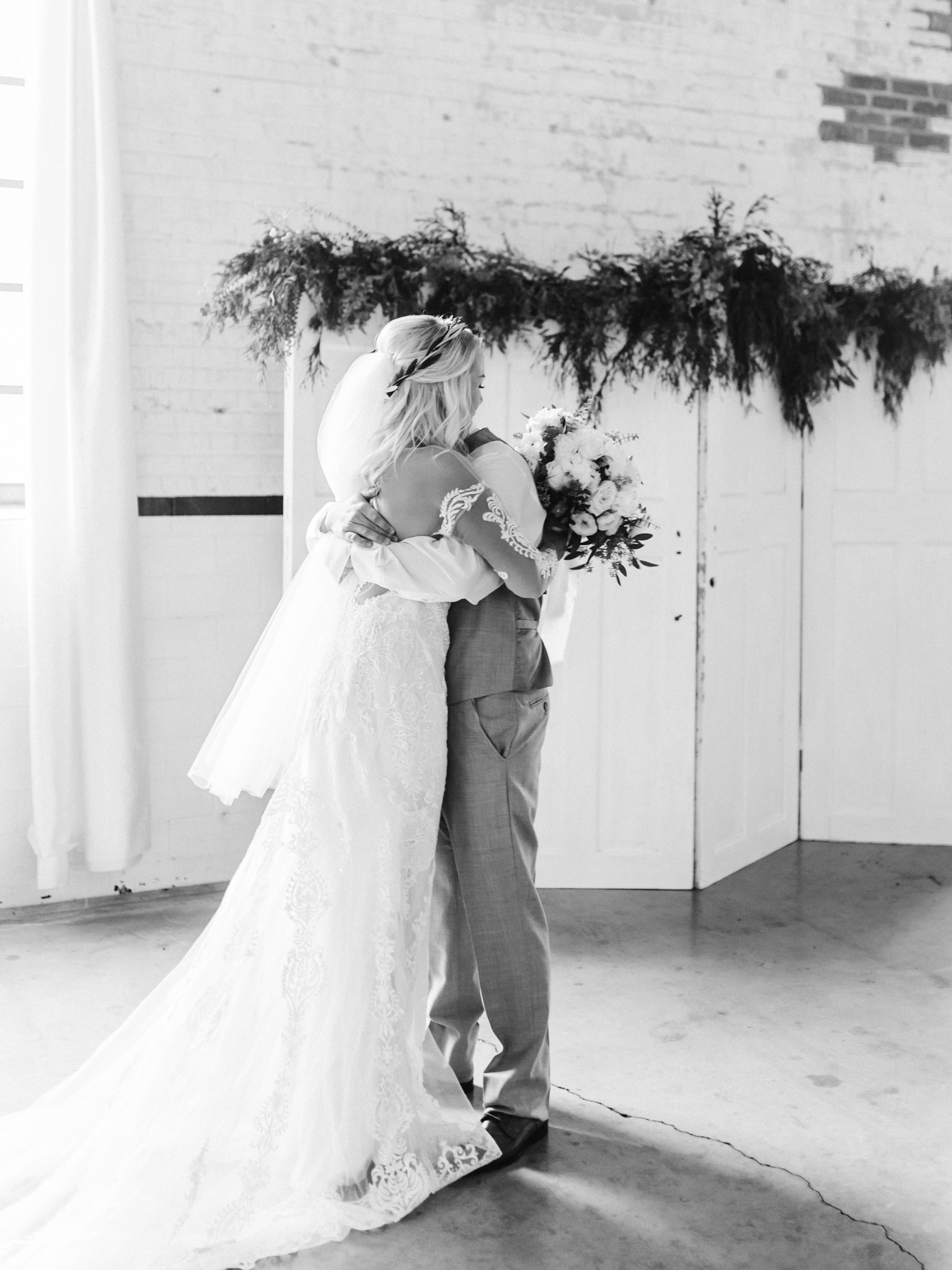 A bride and groom hug while seeing each other for the first time during their first look at their wedding at The Brick