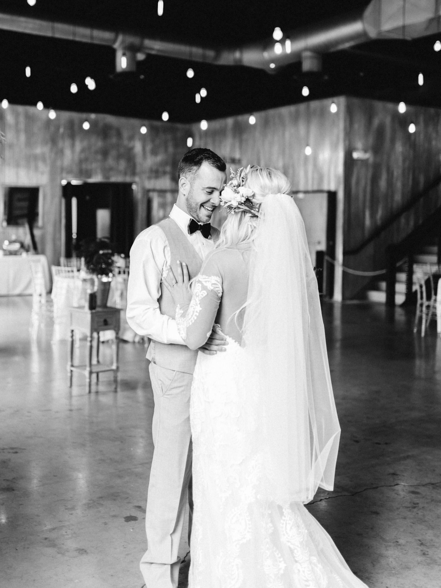 A smiling groom embraces his bride after seeing her for the first time during their first look at The Brick wedding venue